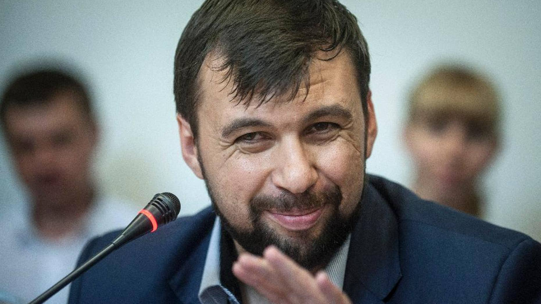 """FILE - In this Wednesday May 14, 2014 file photo Denis Pushilin, leader of the insurgency that has declared an independent """"people's republik"""" in the Donetsk region, speaks at a news conference in eastern Ukraine city of Donetsk.  The Donetsk People's Republic is starting to smell. Rotting garbage is piling up in the hallways of the government office building seized by separatists in eastern Ukraine. Telephones ripped from the walls are piled atop broken furniture and mounds of old files. The stench of sweat and stale cigarettes is everywhere.  The guards, slouching men with pistols shoved in their pockets or flapping loosely in holsters, look increasingly bored.  (AP Photo/Evgeniy Maloletka, File)"""