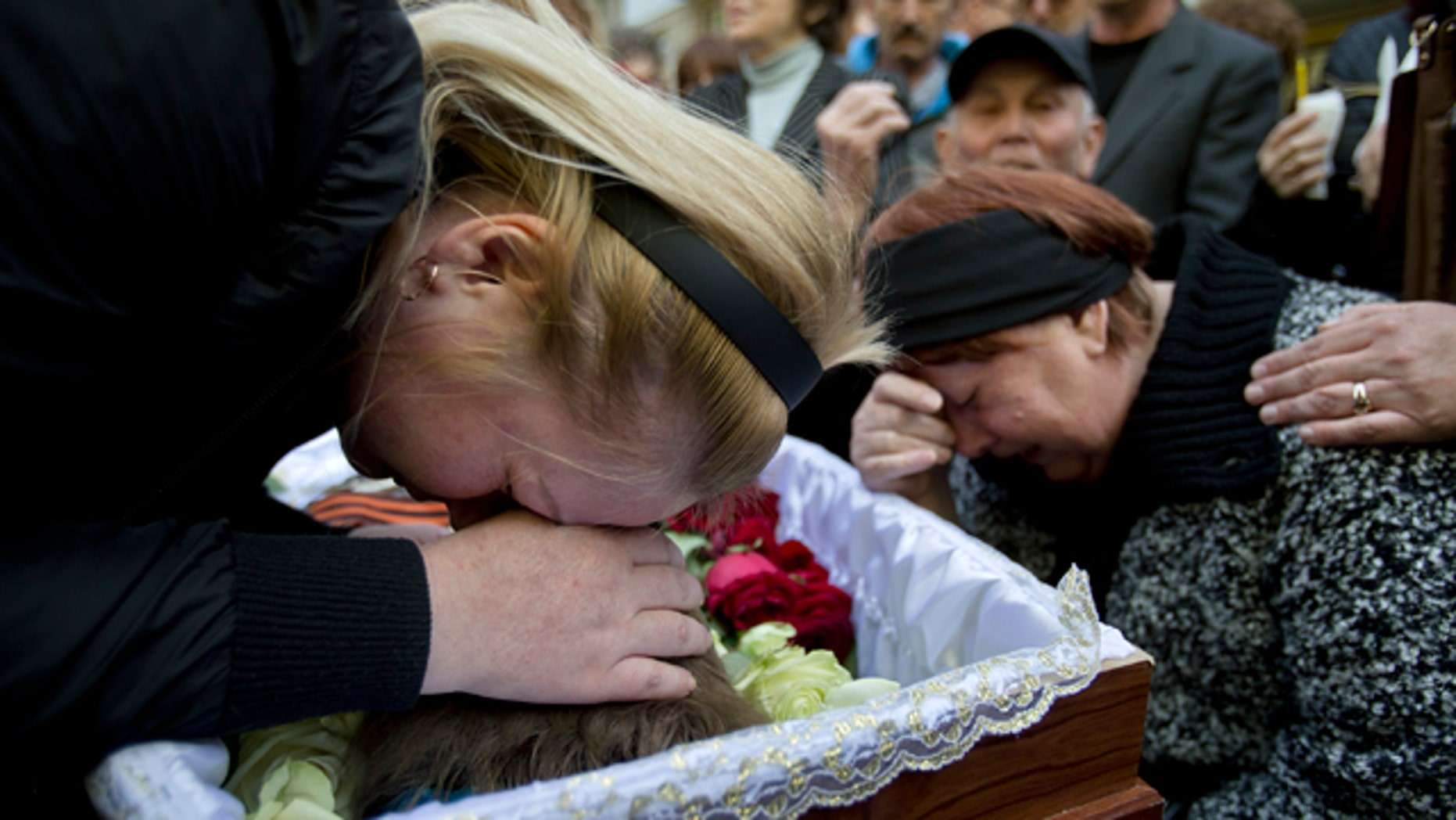 May 6, 2014: Relatives cry around the coffin of 17 year-old Vadim Papura during a religious service outside his apartment block, in Odessa, Ukraine. Papura died after jumping out of the trade union building in an attempt to escape a fire that killed most of the 40 people that died after riots erupted last Friday. (AP Photo/Vadim Ghirda)