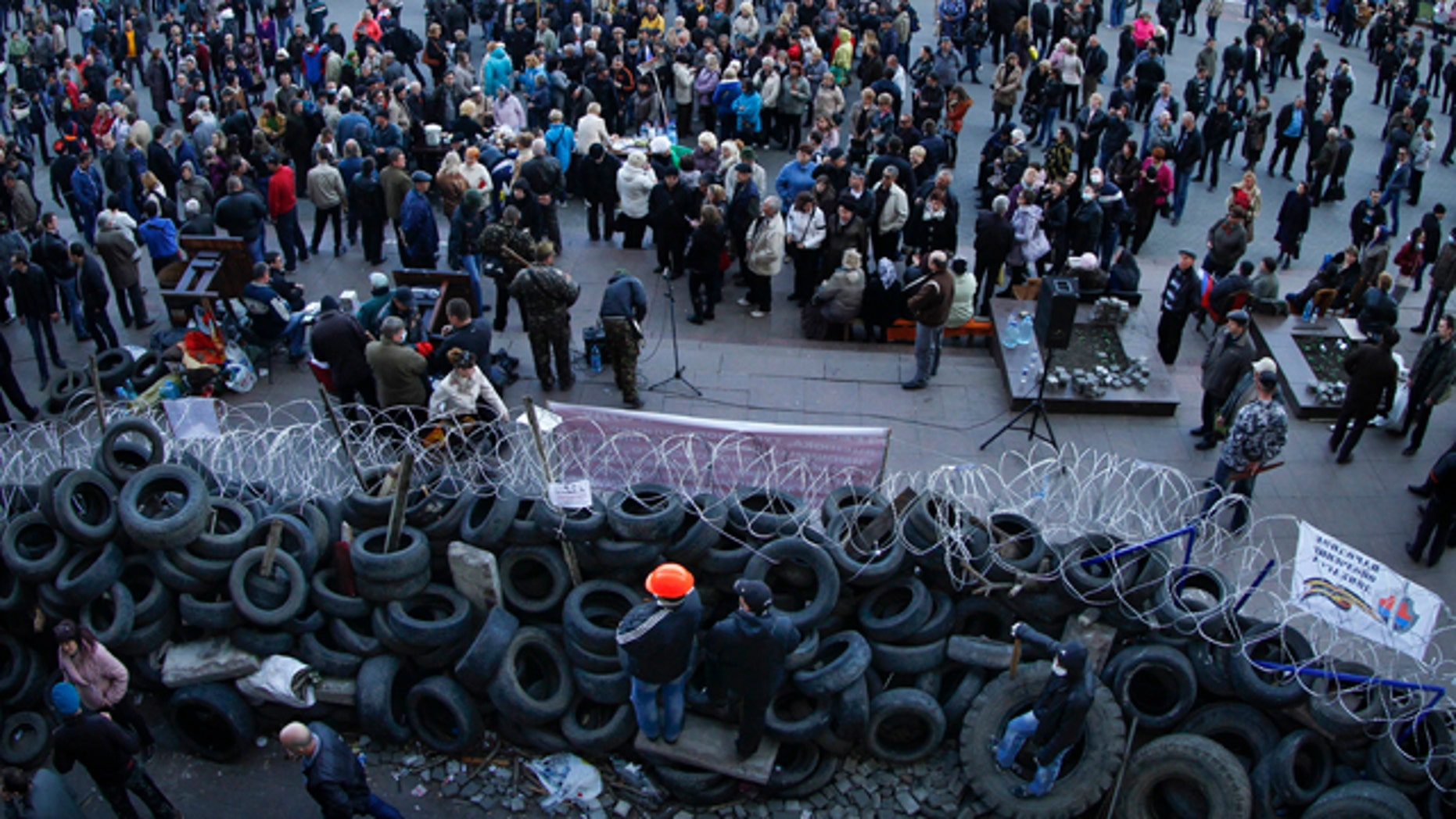 April 7, 2014: People gathered in front of a barricade at the regional administration building in Donetsk, Ukraine.   (AP Photo/Andrey Basevych)