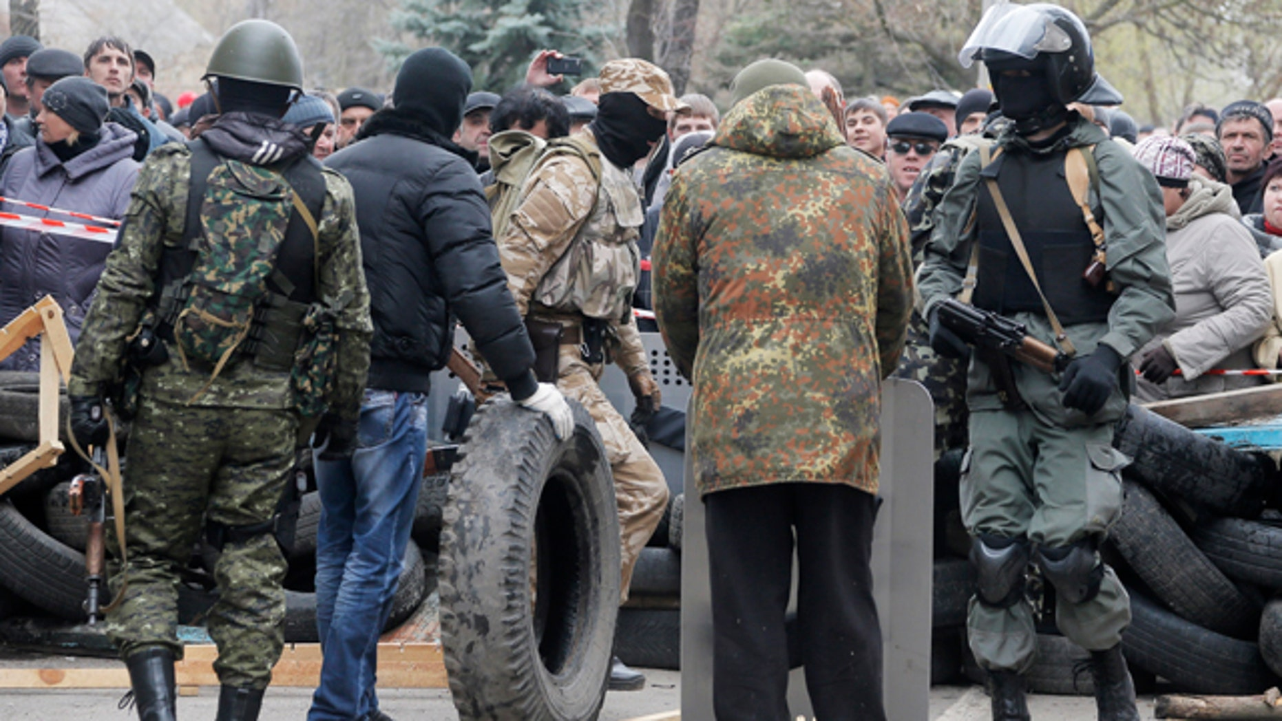 April 12, 2014: Armed pro-Russian activists occupy the police station and build a barricade as people watch on, in the eastern Ukrainian town of Slovyansk. Pro-Moscow protesters have seized a number of government buildings in the east over the past week, undermining the authority of the interim government in the capital, Kiev. (AP Photo/Efrem Lukatsky)