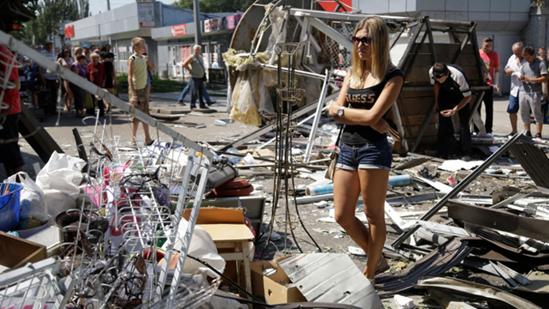 August 6, 2014: Residents inspect the damage after night shelling on a market in Donetsk, eastern Ukraine. Airstrikes and artillery fire between pro-Russian separatists and Ukrainian troops have brought the violence closer than ever to the city center, as Kiev's forces move in on the rebel stronghold. (AP Photo/Sergei Grits)
