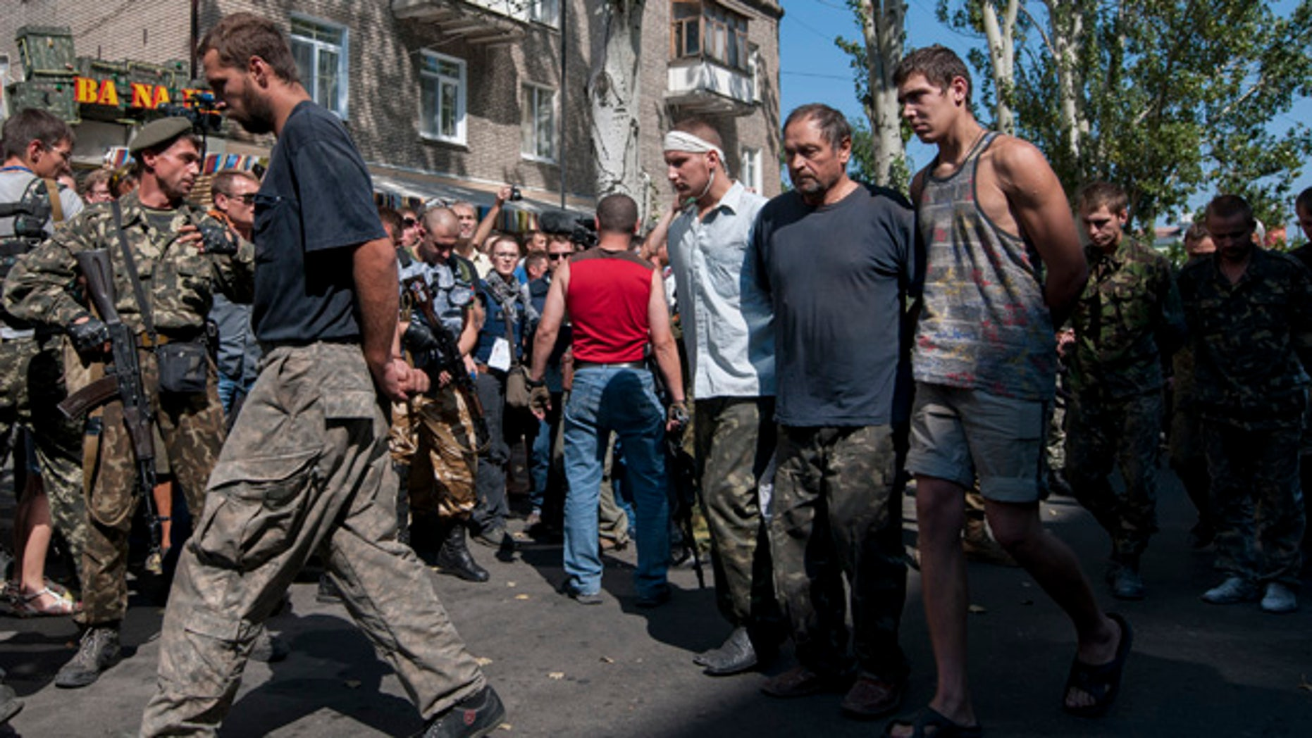 August 24, 2014: Pro-Russian rebels escort captured Ukrainian army prisoners in a central square in Donetsk, eastern Ukraine. (AP Photo/Antoine E.R. Delaunay)