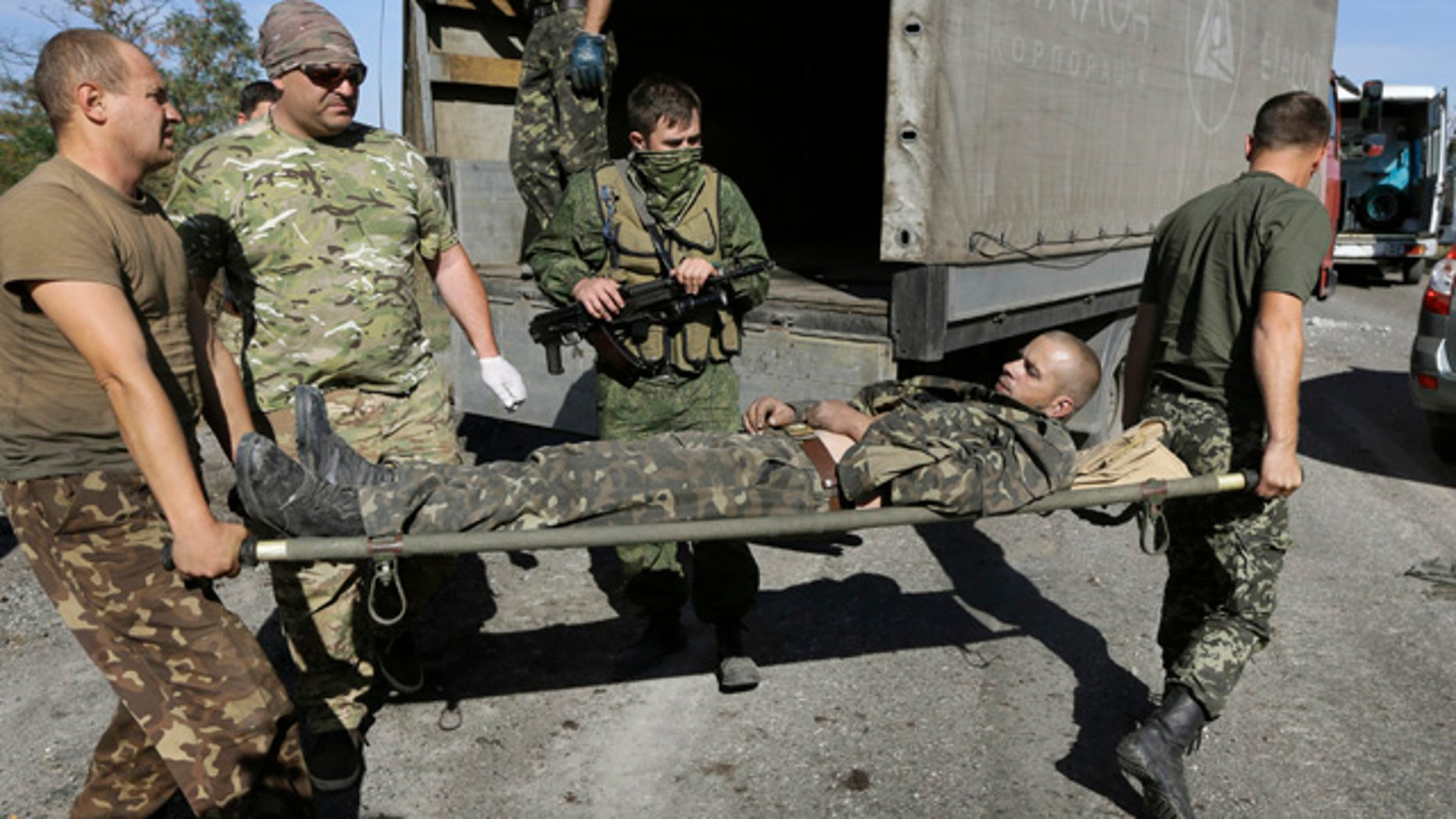 August 30, 2014: Ukrainian army personnel carry an Ukrainian government soldier injured by tank fire to an ambulance in the rebel-held town of Starobesheve.  Half an hour later the soldier died.  (AP Photo/Sergei Grits)