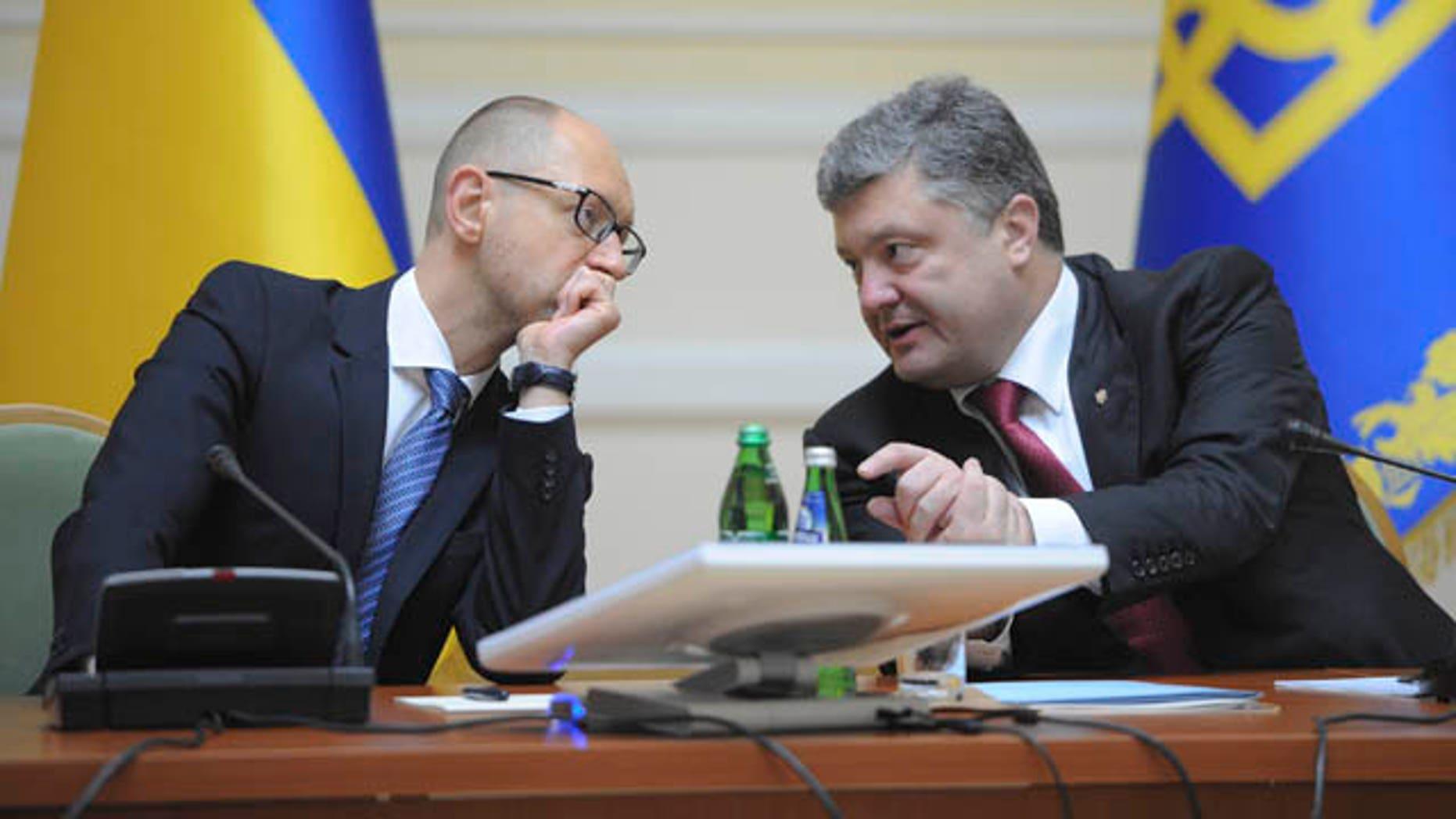 September 10, 2014: Ukrainian President Petro Poroshenko, right, talks with Prime Minister Arseniy Yatsenyuk in Kiev, Ukraine. (AP Photo/Andrew Kravchenko, Pool)
