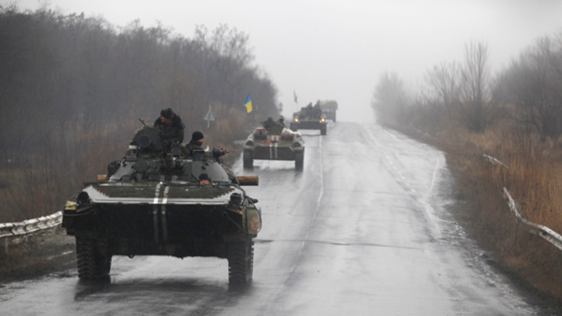 Feb. 1, 2015: Ukranian military vehicles are seen driving on the road towards the town of Artemivsk. Fighting between government and Russian-backed separatist forces in eastern Ukraine has intensified in recent days as rebels seek to encircle the town of Debaltseve, which hosts a strategically important railyway hub. (AP Photo/Petr David Josek)