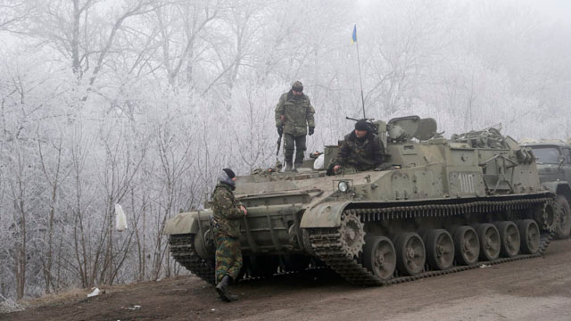 Feb. 15, 2015: Ukrainian government soldiers rest by armored vehicle on the road between the towns of Dabeltseve and Artemivsk. (AP Photo/Petr David Josek)
