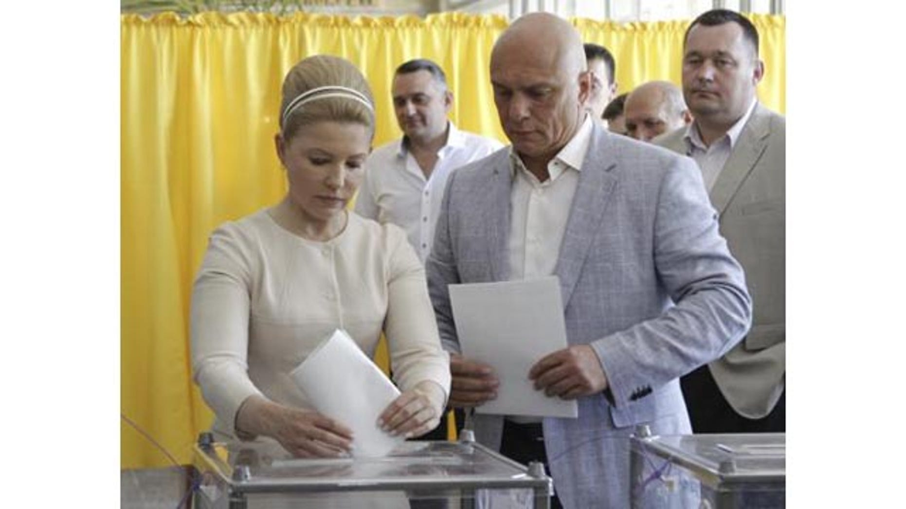May 25, 2014: Former prime minister and Presidential candidate Yulia Tymoshenko (L), accompanied by her husband Oleksander (R), casts her vote during a presidential election at a polling station in Dnipropetrovsk, Ukraine. (Reuters)