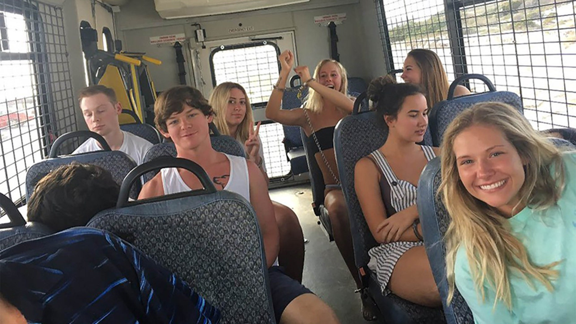 A bus full of 14 underage drinkers posed for the camera on their way to jail.