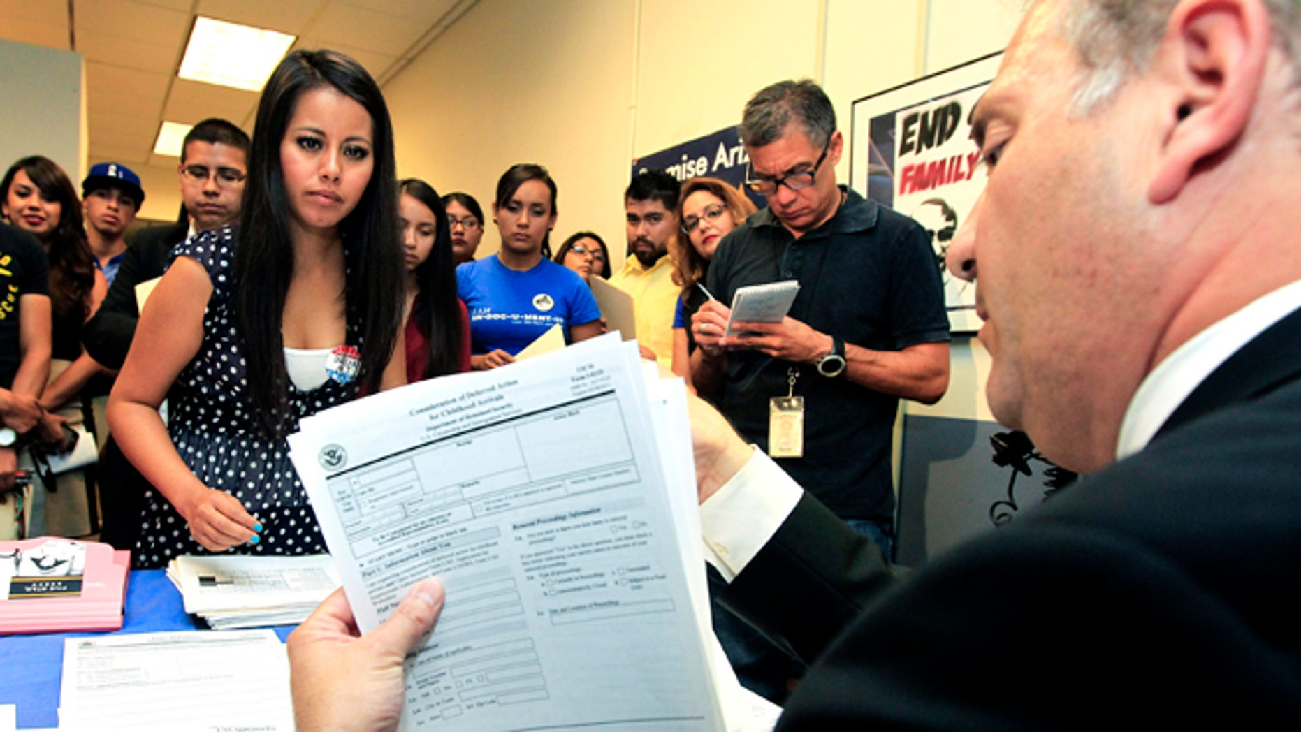 This Aug. 15, 2012 photo shows, Young immigrants, including Gaby Perez, left, hands over all her paperwork to get guidance from immigration attorney Jose Penalosa, right, for a new federal program, called Deferred Action, that would help them avoid deportation in Phoenix.   Schools and consulates have been flooded with requests for documents after President Barack Obama announced a new program allowing young illegal immigrants to apply for two-year renewable work permits. (AP Photo/Ross D. Franklin)