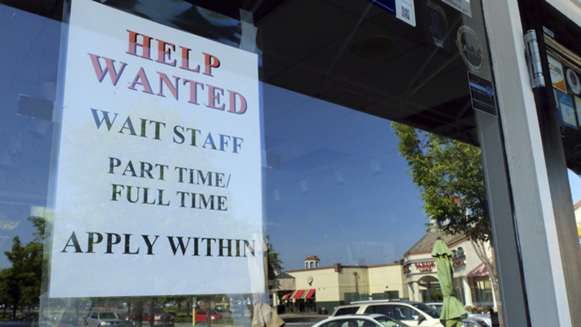 In  this , Friday, June 21, 2013, photo, a Help Wanted sign is displayed in the window of a restaurant at a shopping center in Charlotte, N.C.  The Labor Department reports on the number of Americans who applied for unemployment benefits last week on July 11, 2013. (AP Photo/Chuck Burton)