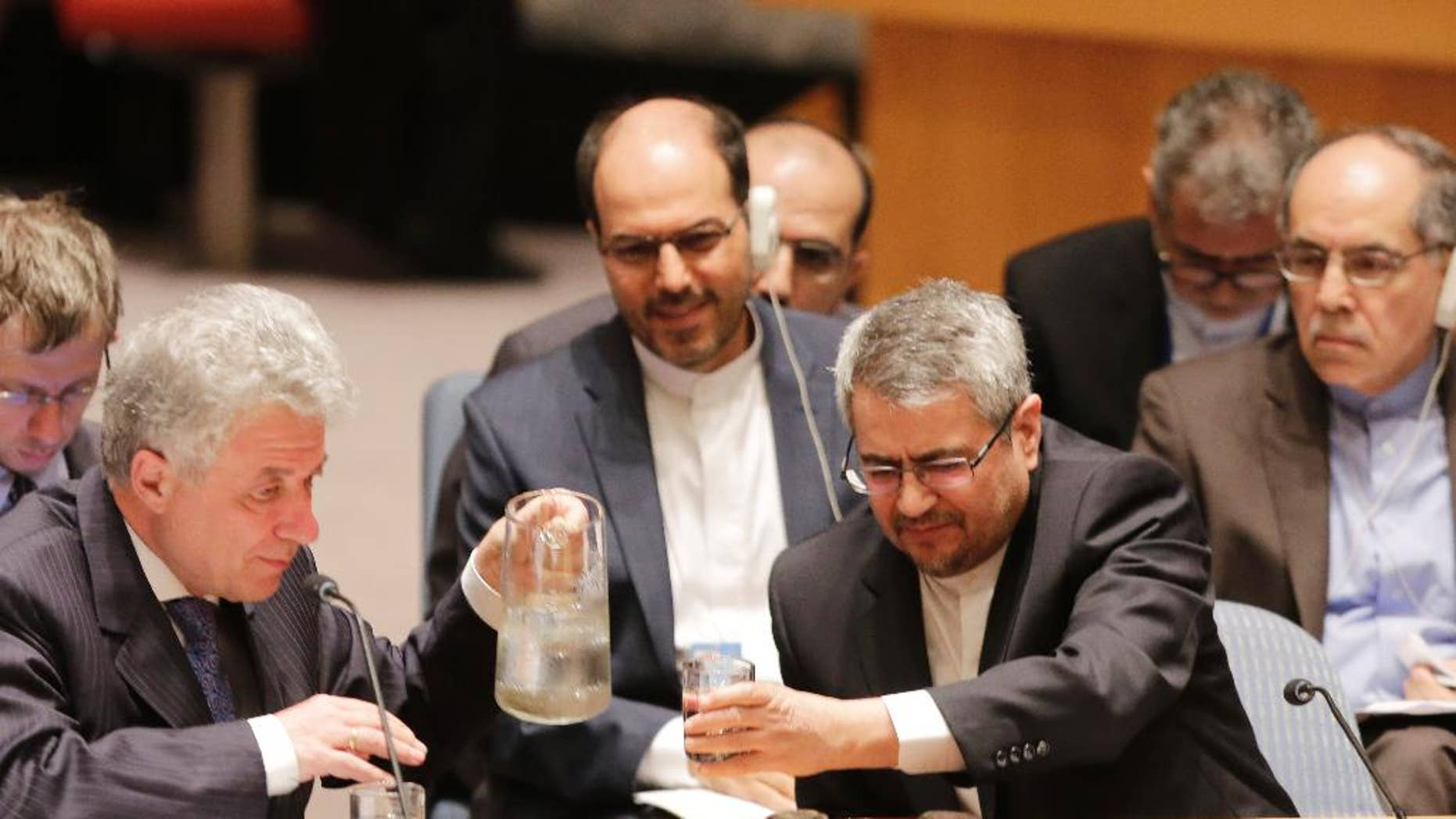 Thomas Mayr-Harting, left, head of the delegation of the European Union to the United Nations, pours a glass of water for Iran's U.N. Ambassador, Gholamali Khoshroo, at United Nations headquarters, Monday, July 20, 2015. The U.N. Security Council on Monday unanimously endorsed the landmark nuclear deal between Iran and six world powers and authorized a series of measures leading to the end of U.N. sanctions that have hurt Iran's economy. (AP Photo/Mark Lennihan)