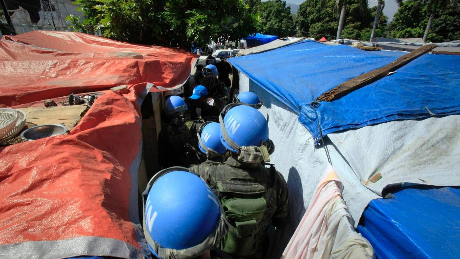 "FILE - In this Tuesday, March 30, 2010 file photo, United Nations peacekeepers patrol an earthquake survivors makeshift camp in Port-au-Prince. In 2015, troubled by peacekeepers' sexual relationships with the people they are meant to protect, the UN has quietly started helping with DNA collection to prove paternity claims for so-called ""peacekeeper babies."" (AP Photo/Jorge Saenz)"