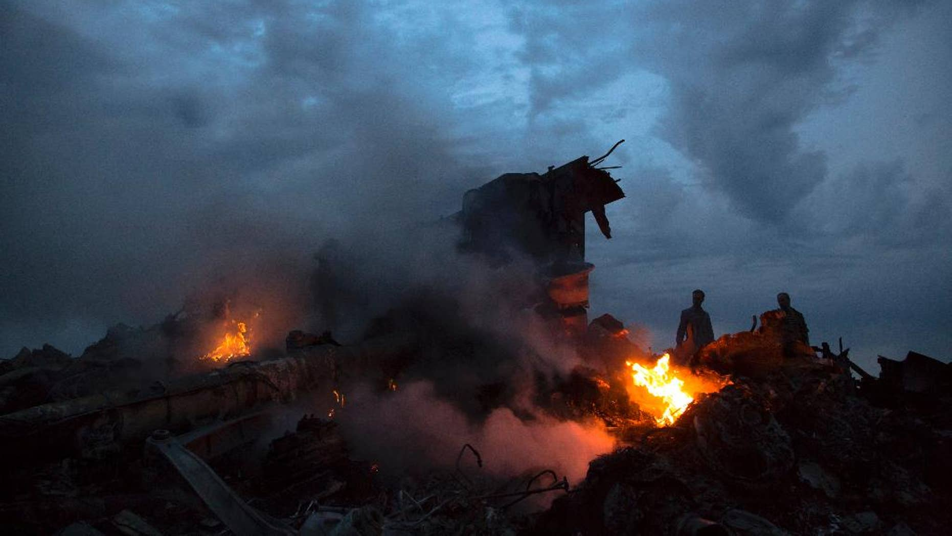File - This July 17, 2014, file photo shows people walking amongst burning debris at the crash site of Malaysia Airlines Flight 17 near the village of Hrabove, eastern Ukraine.  Ukraine said the passenger plane was shot down as it flew over the country, killing all 298 people on board. A series of unanswered questions about the downing the flight shows the limits of U.S. intelligence-gathering even when it is intensely focused, as it has been in Ukraine since Russia seized Crimea in March. (AP Photo/Dmitry Lovetsky, File)