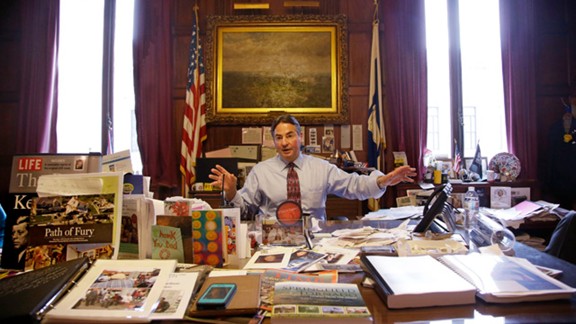 June 5, 2014: Springfield Mayor Domenic Sarno sits behind his city hall desk reiterating the position he has taken with the United States State Department against accepting any more resettled refugees in Springfield, Mass. (AP Photo/Stephan Savoia)