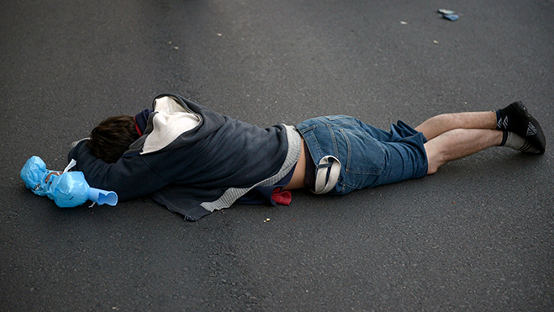 A fan of Uruguay's national soccer team lies on the ground as he reacts despondenlty, after his team lost to Costa Rica, in downtown in Montevideo, Uruguay, Saturday, June 14, 2014. Costa Rica upset Uruguay 3-1 in the first game of group D of the Soccer World Cup. (AP Photo/Matilde Campodonico)