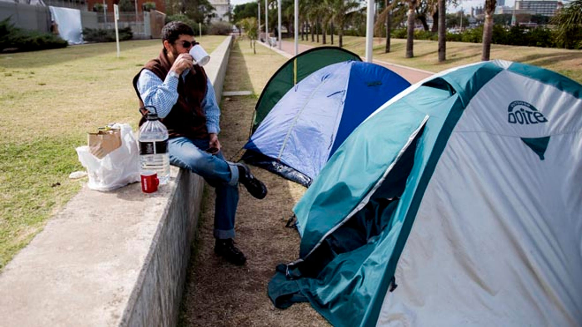 FILE - In this May 6, 2015 file photo, Omar Abdelhadi Faraj drinks tea in front of his tent outside the U.S. embassy as a form of protest in Montevideo, Uruguay. Faraj's attorney Mauricio Pigola said Sunday, Jan. 24, 2016 that his client was released after a judge found insufficient evidence against him in a domestic violence case. Faraj is a Syrian who arrived to Uruguay in December 2014 with five other ex-prisoners once held with terror suspects at the U.S. military base in Guantanamo, Cuba. (AP Photo/Matilde Campodonico, File)
