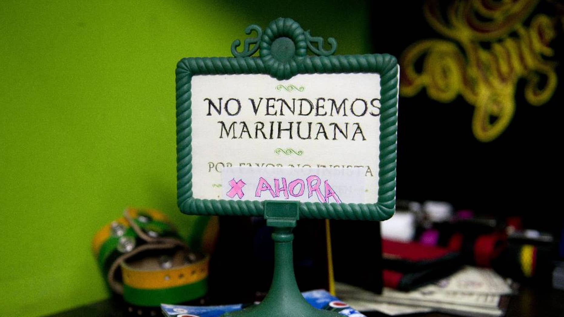 """FILE - This May 6, 2014 file photo shows a sign that reads in Spanish; """"We don't sell pot, yet,"""" on display at a head shop in downtown Montevideo, Uruguay. Delays in implementing the plan to create the world's first national, government-regulated marketplace for legal pot , are putting it at risk as polls point to opposition gains in October general elections and disapproval of the project by most Uruguayans. (AP Photo/Matilde Campodonico, File)"""