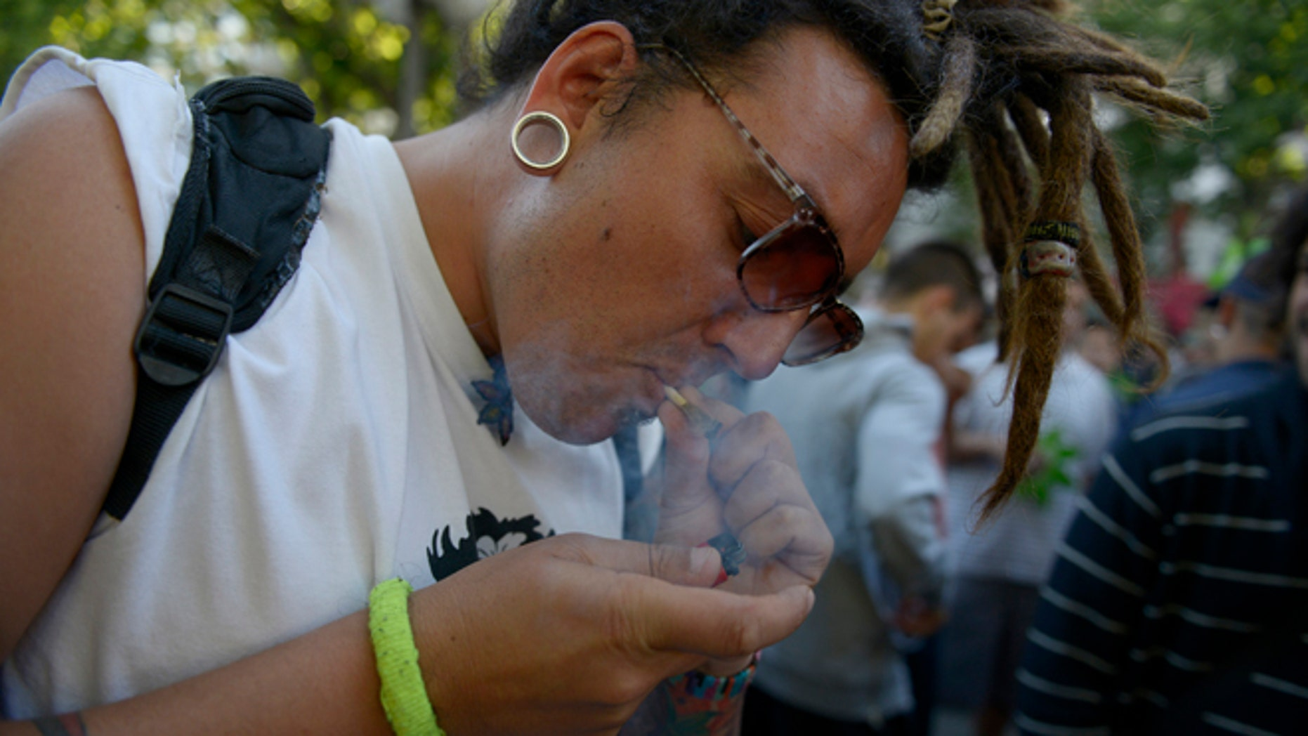 A man smokes a marijuana cigarette during a demonstration in support of the legalization of marijuana outside the Congress in Montevideo, Uruguay, Tuesday, Dec. 10, 2013. Uruguay's Senate was finishing its final debate Tuesday before voting on a plan to create the world's first national marijuana market, with the state regulating the entire process of growing, selling and using a drug that is illegal almost everywhere else. (AP Photo/Matilde Campodonico)
