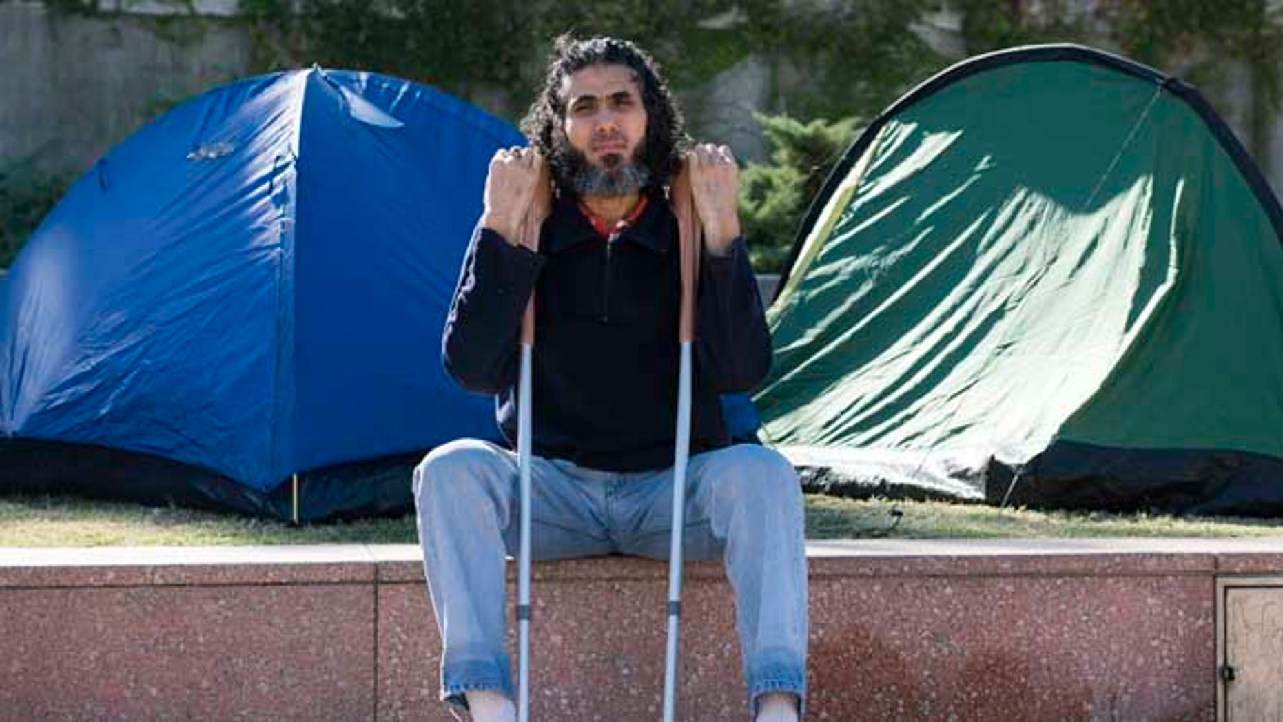 In this May 5, 2015 photo, former Guantanamo detainee Abu Wa'el Dhiab from Syria sits in front of the U.S. embassy while visiting former fellow detainees who were demanding financial assistance from the U.S., in Montevideo, Uruguay. Dhiab, who resettled in Uruguay, was briefly hospitalized Monday, Sept. 5, 2016, after becoming weak from a hunger strike. Dhiab is demanding that he be allowed to leave the South American country. Uruguay took in Dhiab and five other former Guantanamo prisoners for resettlement in 2014. (AP Photo/Matilde Campodonico)