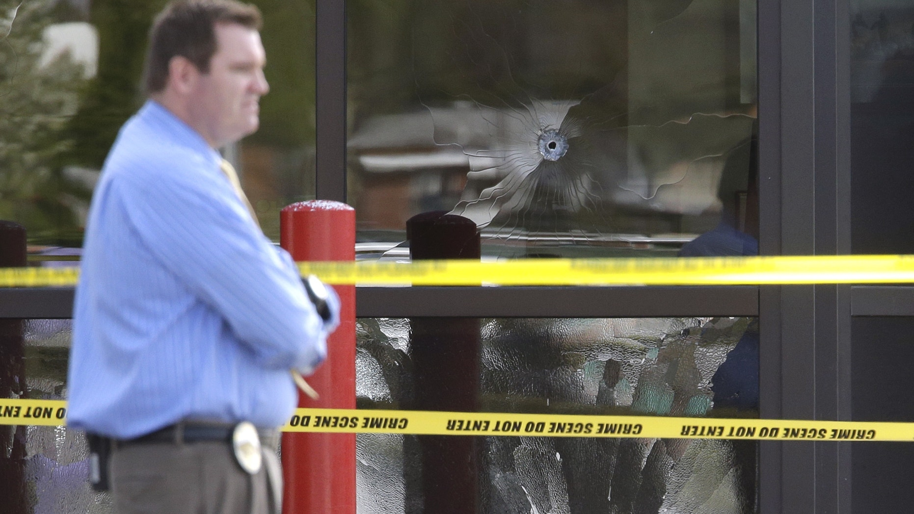 April 29, 2013: A West Valley City Police Officer stands near a bullet shattered window at the West Valley City Police Department in West Valley City, Utah.