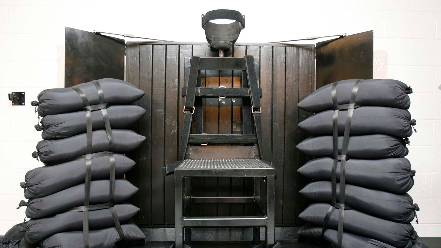 The execution chamber at the Utah State Prison after Ronnie Lee Gardner was executed by firing squad Friday, June 18, 2010. The bullet holes are visible in the wood panel behind the chair. Gardner was convicted of aggravated murder, a capital felony, in 1985. (AP Photo/Trent Nelson - Pool)