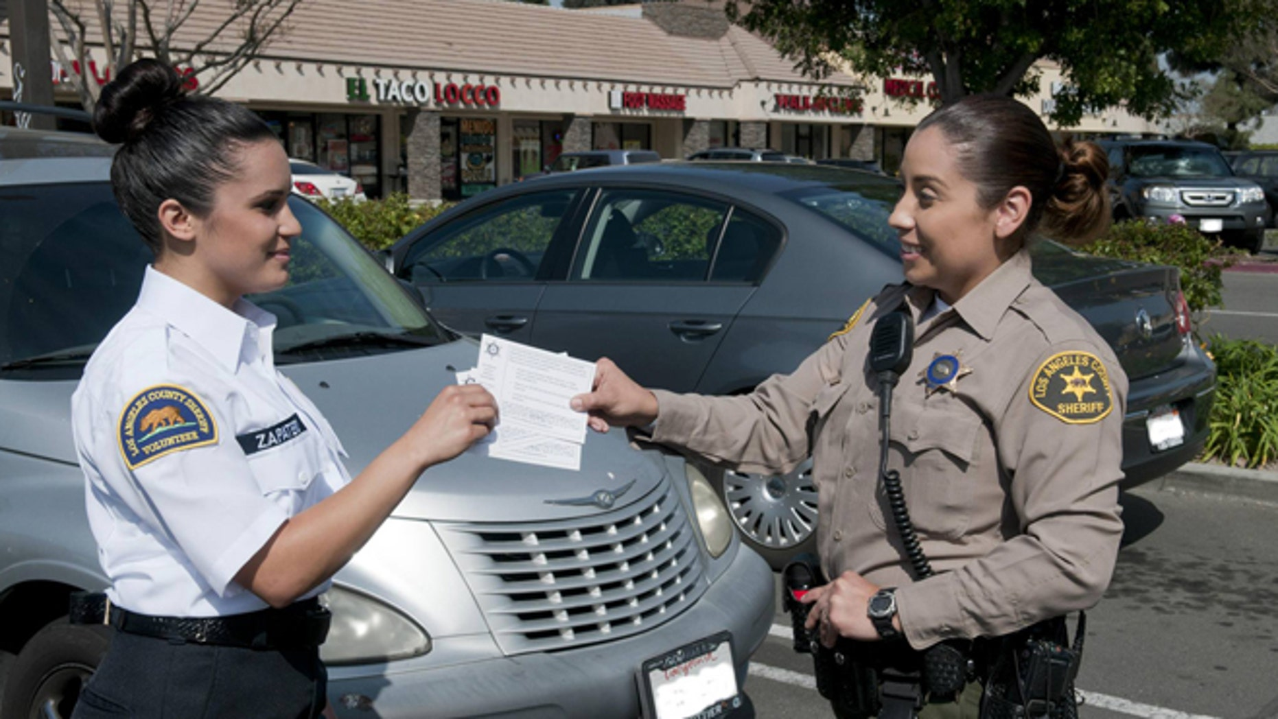 A deputy hands crime prevention tips to a Los Angeles County Sheriff's Department civilian volunteer, who are now allowed to issue parking violations to Malibu residents. (Courtesy: LASCD)