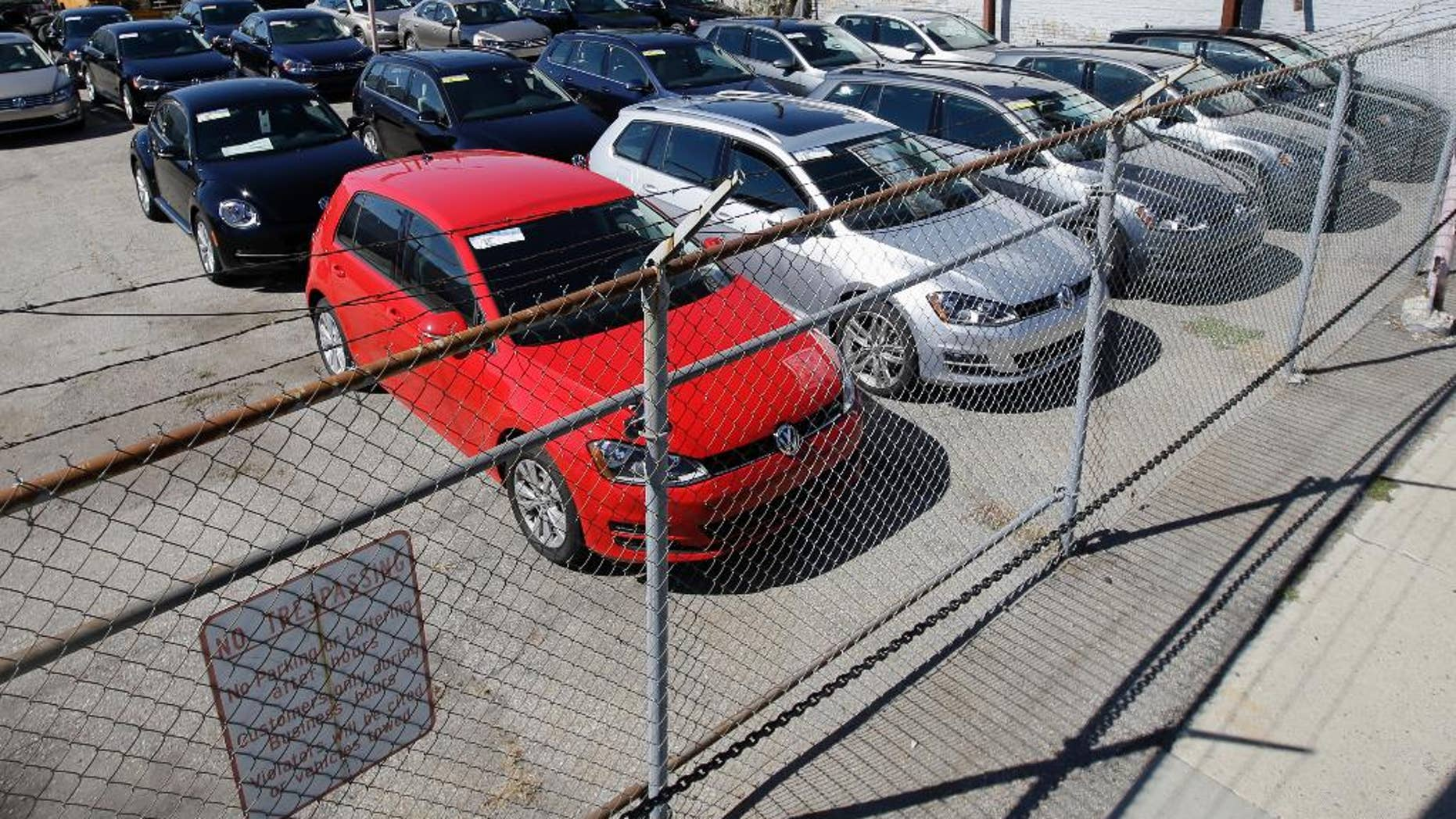 """FILE - In this Sept. 23, 2015 file photo, diesel Volkswagens are seen behind a security fence on a storage lot near a VW dealership in Salt Lake City. Volkswagen is far from the first company to stand accused of trying to game required emissions tests. Almost since the passage of the Clean Air Act in 1970, major manufacturers of cars, trucks and heavy equipment have been busted for using what regulators call """"defeat devices"""" _ typically programing a vehicle's on-board computer to boost horsepower or fuel mileage by belching out dirtier exhaust than allowed. (AP Photo/Rick Bowmer, File)"""