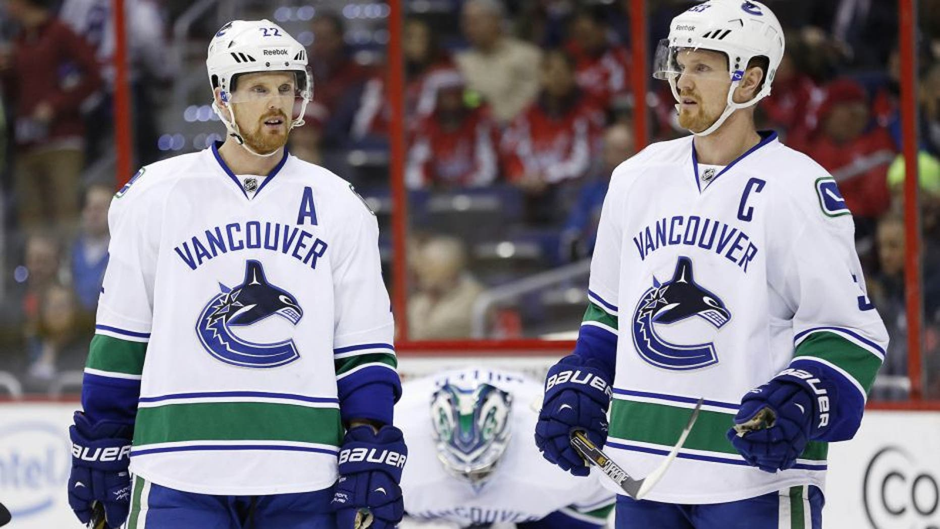 Dec 2, 2014; Washington, DC, USA; Vancouver Canucks left wing Daniel Sedin (22) and Canucks center Henrik Sedin (33) stand on the ice against the Washington Capitals in the first period at Verizon Center. Mandatory Credit: Geoff Burke-USA TODAY Sports