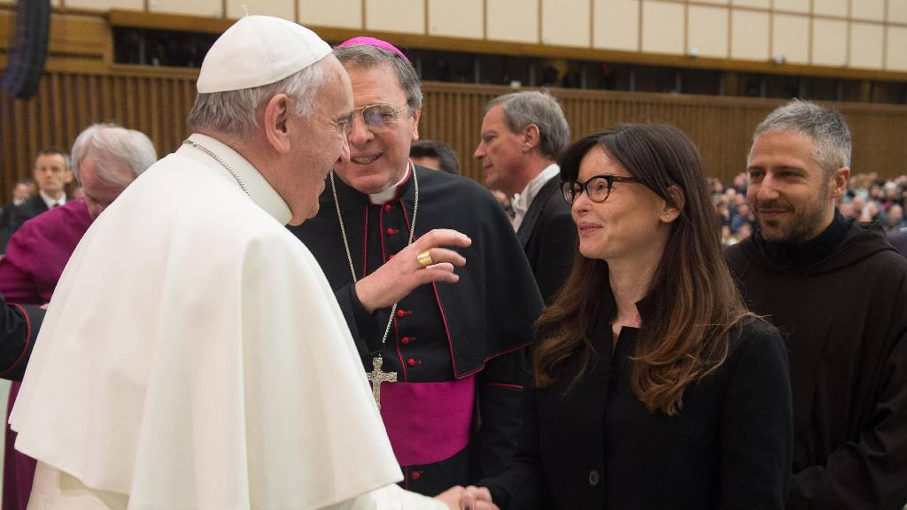 FILE -- In this file photo taken at the Vatican, on Feb. 4, 2015, Pope Francis shakes hands with Italian lawyer Lucia Annibali during the weekly general audience in the Pope Paul VI hall, . Annibali, became a symbol in the fight against men's violence toward women, after suffering in the 2013 an acid attack masterminded by her ex-boyfriend Luca Varani, also a lawyer. Varani has been convicted and sentenced to 20 years in prison for ordering the attack on his ex-girlfriend. Two Albanian men were convicted of throwing the acid and each received a 14 year term. On saturday in a speech, Francis decried disfiguring attacks on women. (AP Photo/L'Osservatore Romano, Pool)