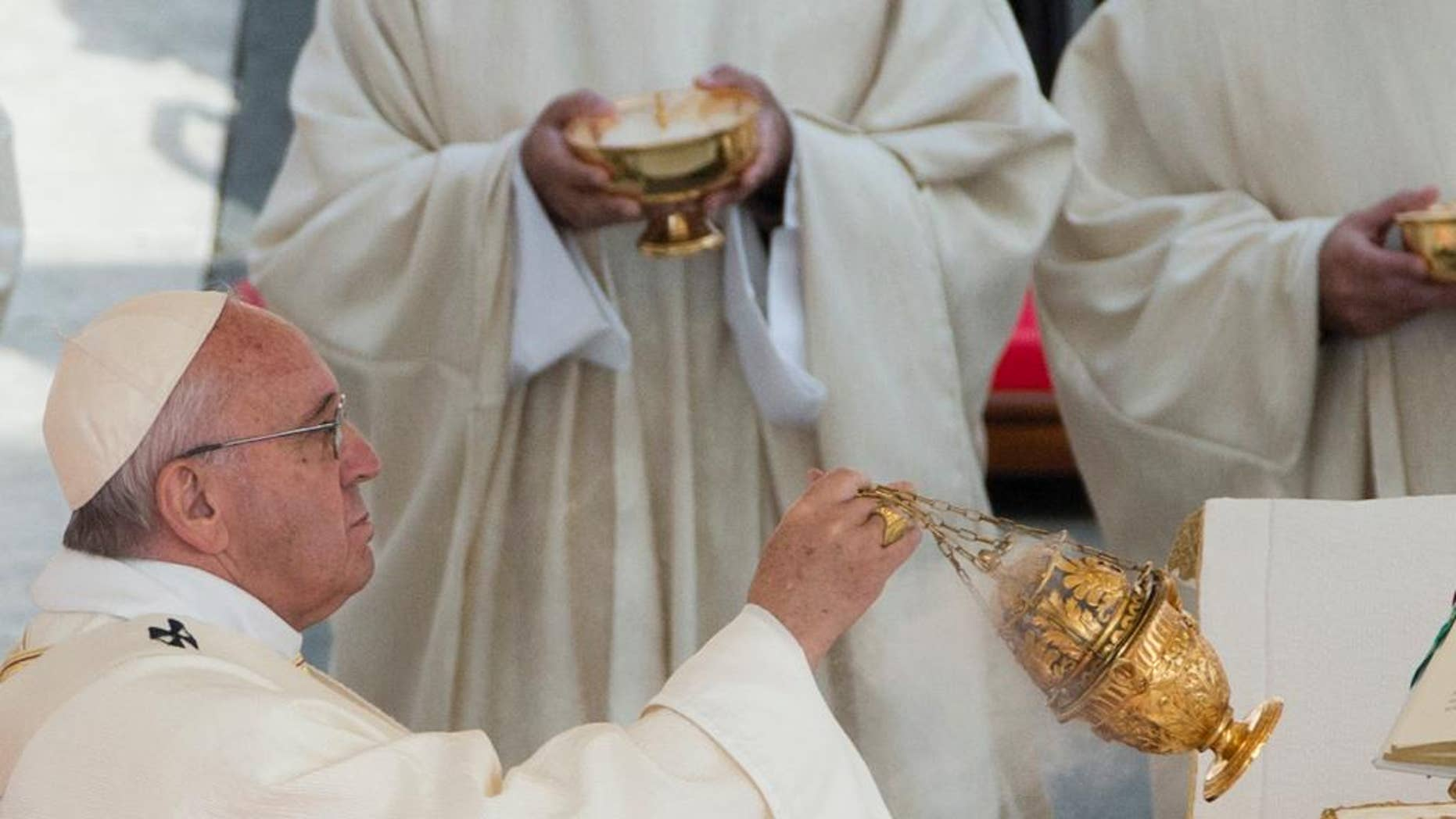 Pope Francis spreads incense during a canonization ceremony in St. Peter's Square at the Vatican Sunday, Oct. 18, 2015. Pope Francis canonized the Catholic Church's first married couple in modern times on Sunday, declaring the parents of the beloved St. Therese of Lisieux saints in their own right. (AP Photo/Alessandra Tarantino)
