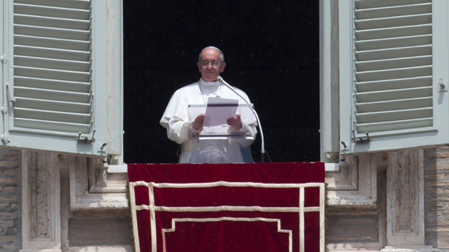 Pope Francis reads a message during the Angelus noon prayer he celebrated from the window of his studio overlooking St. Peter's square at the Vatican, Sunday, June 9, 2013.(AP Photo/Alessandra Tarantino)