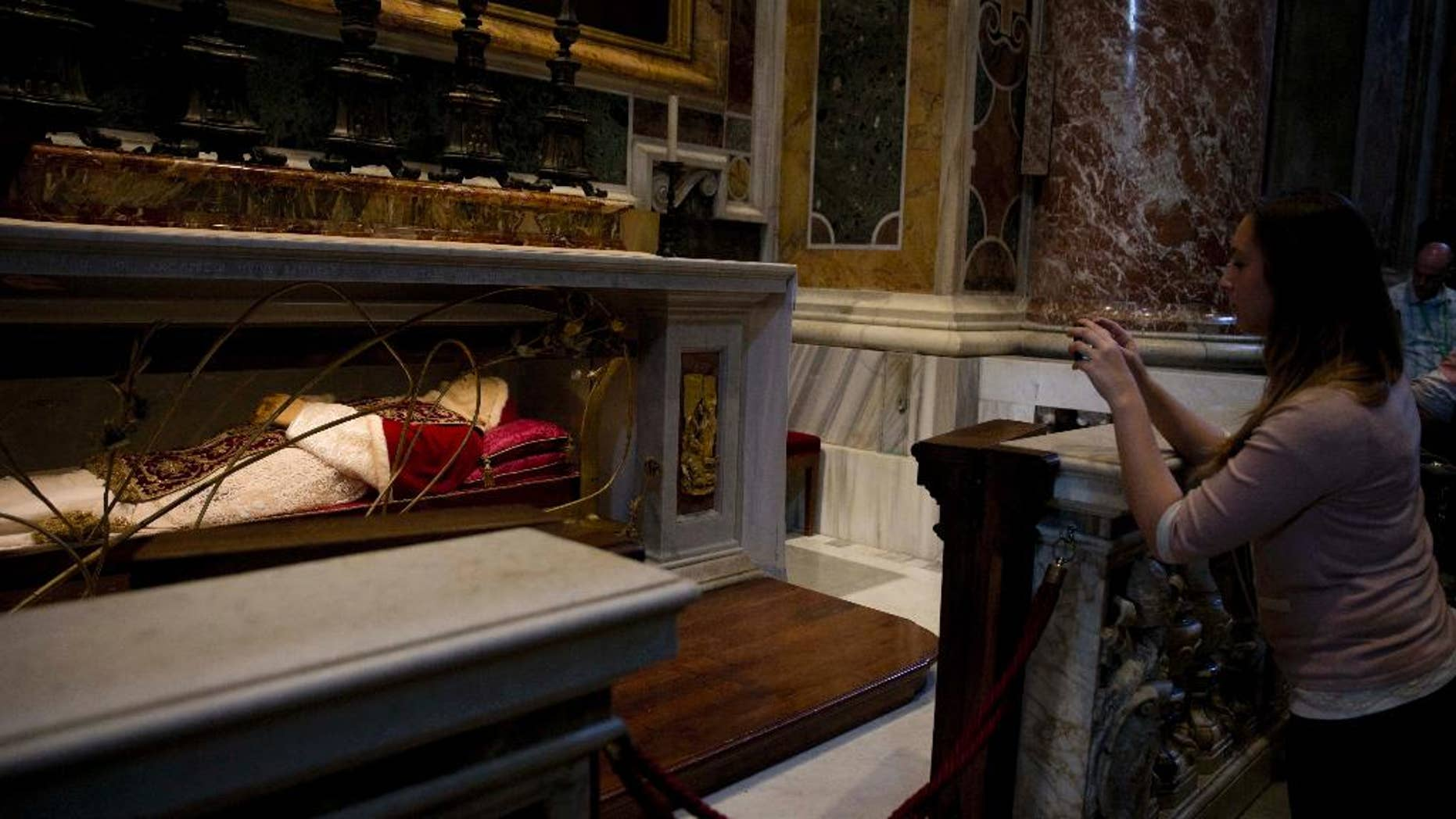 A woman takes pictures of the tomb of Pope John XXIII in St. Peter's Basilica at the Vatican, Thursday, April 24, 2014. Hundred thousands of pilgrims and faithful are expected to reach Rome to attend the scheduled April 27 ceremony at the Vatican in which Pope Francis will elevate in a solemn ceremony John XXIII and John Paul II to sainthood. (AP Photo/Alessandra Tarantino)