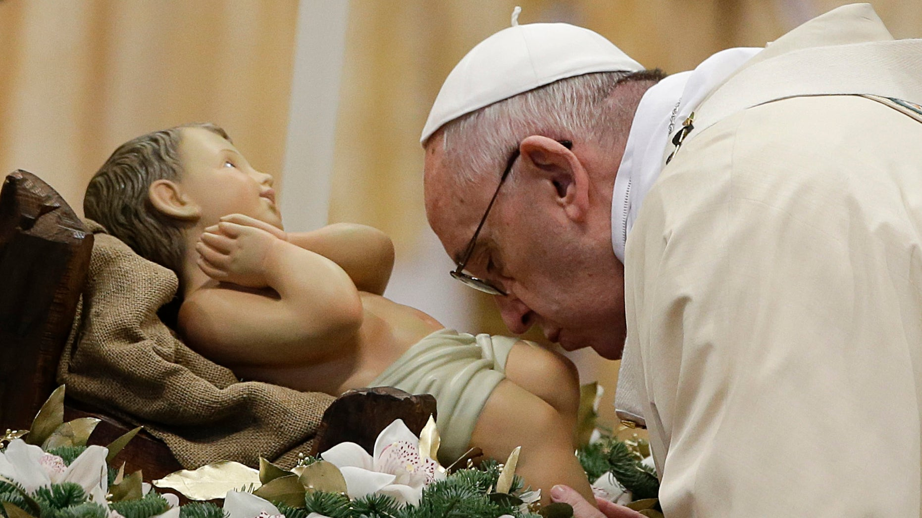Pope Francis kisses during statue of baby Jesus a Mass in St. Peter's Basilica, at the Vatican, to mark Epiphany, Wednesday, Jan. 6, 2016. The Epiphany day is a joyous day for Catholics in which they recall the journey of the Three Kings, or Magi, to pay homage to Baby Jesus (AP Photo/Gregorio Borgia)