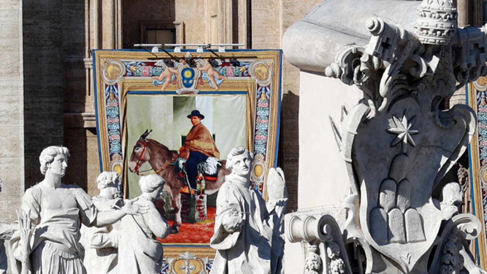 """The tapestry of Argentina's """"gaucho priest"""" Jose Gabriel del Rosario Brochero hangs from the facade of St, Peter's Basilica prior to the start of a Canonization Mass celebrated by Pope Francis in St. Peter's Square, at the Vatican, Sunday, Oct. 16, 2016. The pope canonized Brochero on Sunday along with six others in one of the final big Masses of his Holy Year of Mercy. (AP Photo/Andrew Medichini)"""