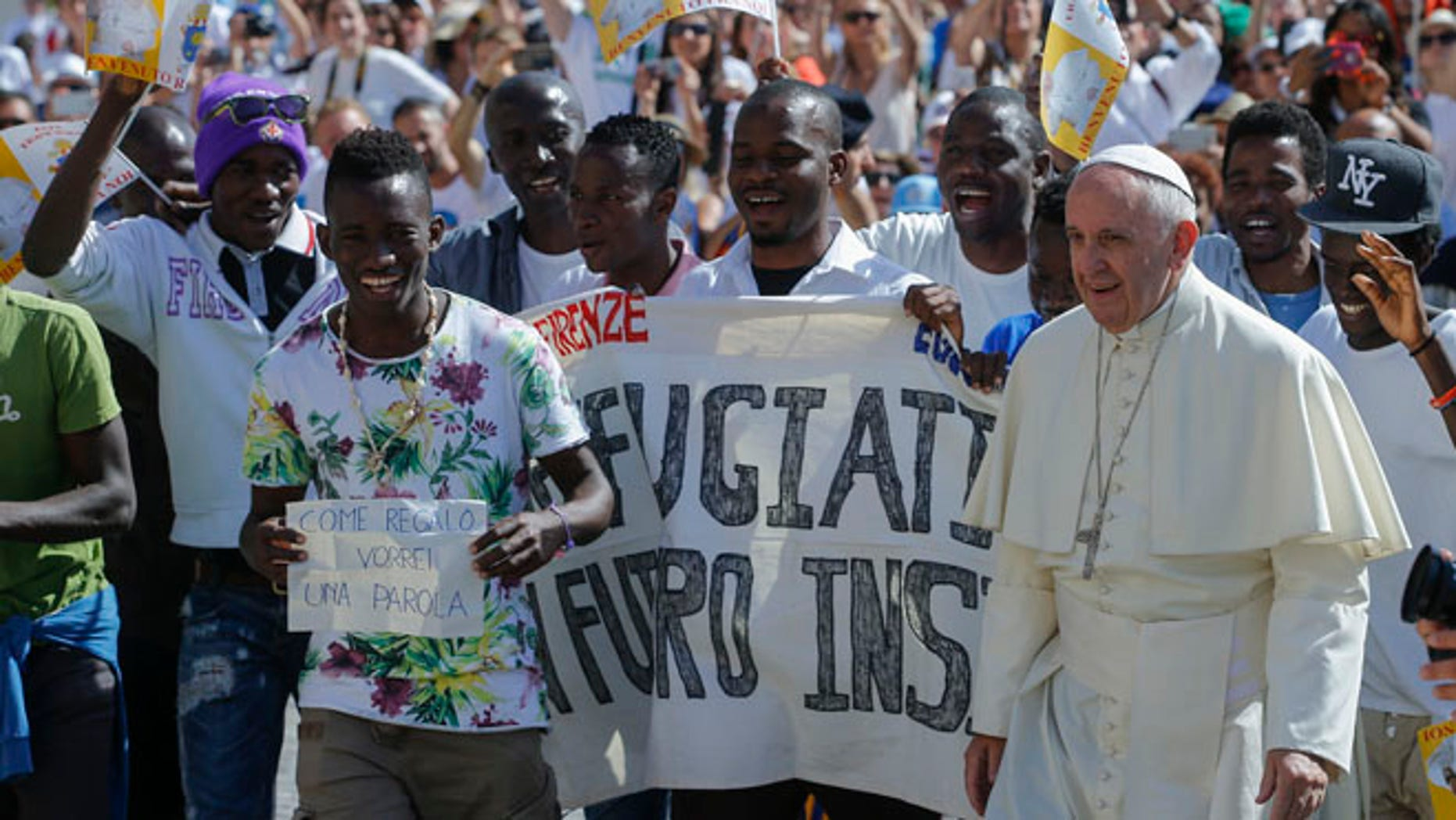 FILE- In this file photo dated Wednesday, June 22, 2016, Pope Francis walks with a group of refugees he invited to join him on the steps of St. Peter's Basilica during his weekly general audience in St. Peter's Square at the Vatican.  Pope Francis begins a five-day visit to Poland on upcoming Wednesday July 27, 2016, and hopes to inspire aid to homeless strangers and acts of mercy for refugees during his visit, although Poland has closed its borders to refugees. (AP Photo/Fabio Frustaci, FILE)