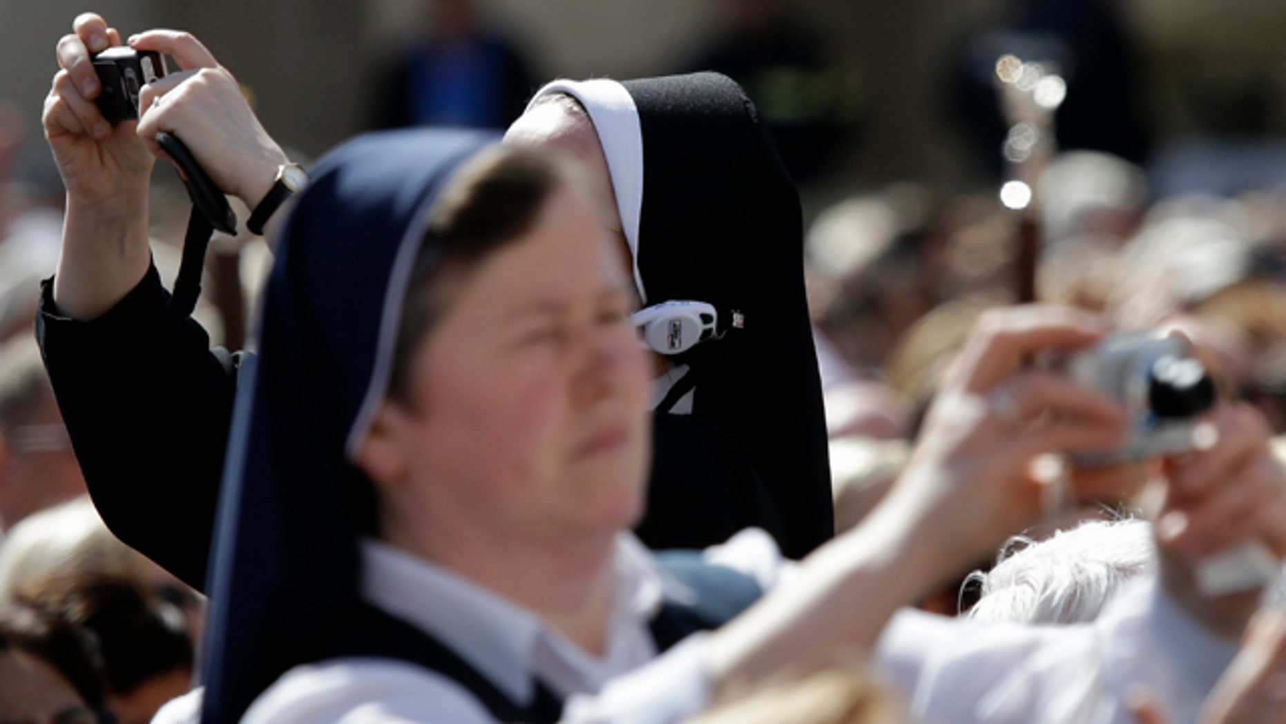 April 28, 2014: Nuns take pictures prior to the start of a thanksgiving mass celebrated by Cardinal Angelo Comastri following Sunday's canonizations of John XXIII and John Paul II, in St. Peter's Square, at the Vatican.(AP Photo/Gregorio Borgia)