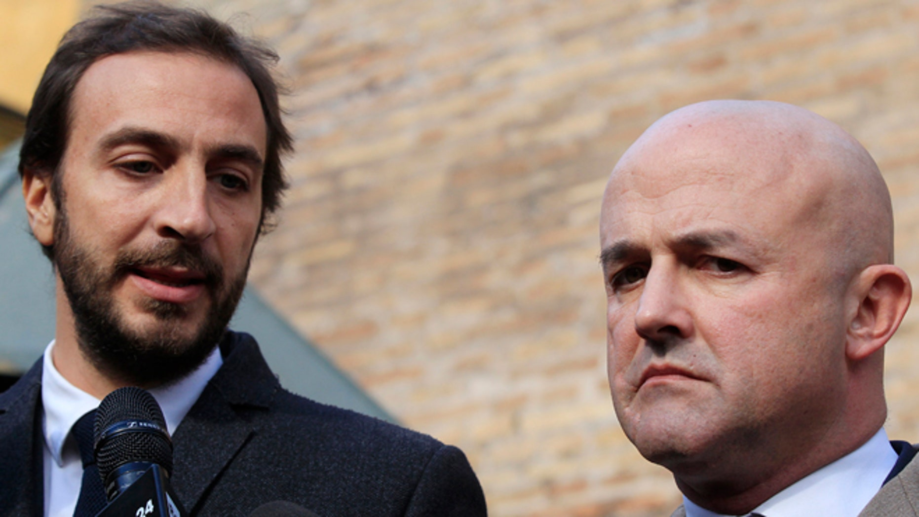 Italian journalists Gianluigi Nuzzi, right, and Emiliano Fittipaldi, talk to reporters outside the Vatican City at the Perugino gate, Tuesday, Nov. 24, 2015. The two Italian journalists who wrote books detailing Vatican mismanagement faced trial on Tuesday in a Vatican courtroom along with three people accused of leaking them the information in a case that has drawn scorn from media watchdogs. (AP Photo/Gregorio Borgia)