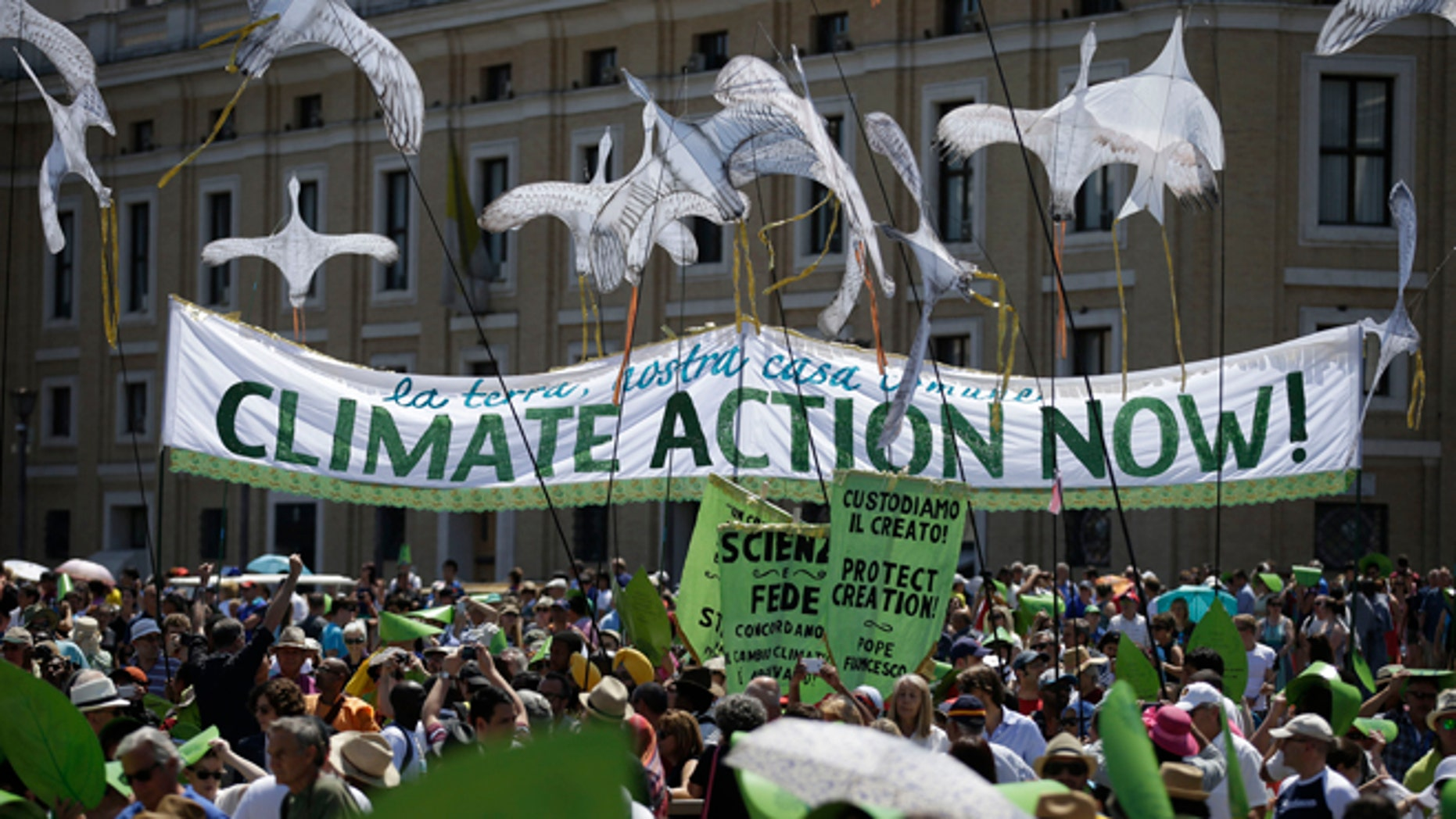 """People hold a banner reading ' Climate action Now ' in St. Peter's Square, at the Vatican, Sunday, June 28, 2015. Greeting people Sunday from his studio window, Francis praised a few hundred people who marched to St. Peter's Square under the banner """"one Earth, one family."""" Marchers included Christians, Muslims, Jews, Hindus and others. Their route began near the French embassy to remind people of a climate change conference in Paris later this year. (AP Photo/Andrew Medichini)"""