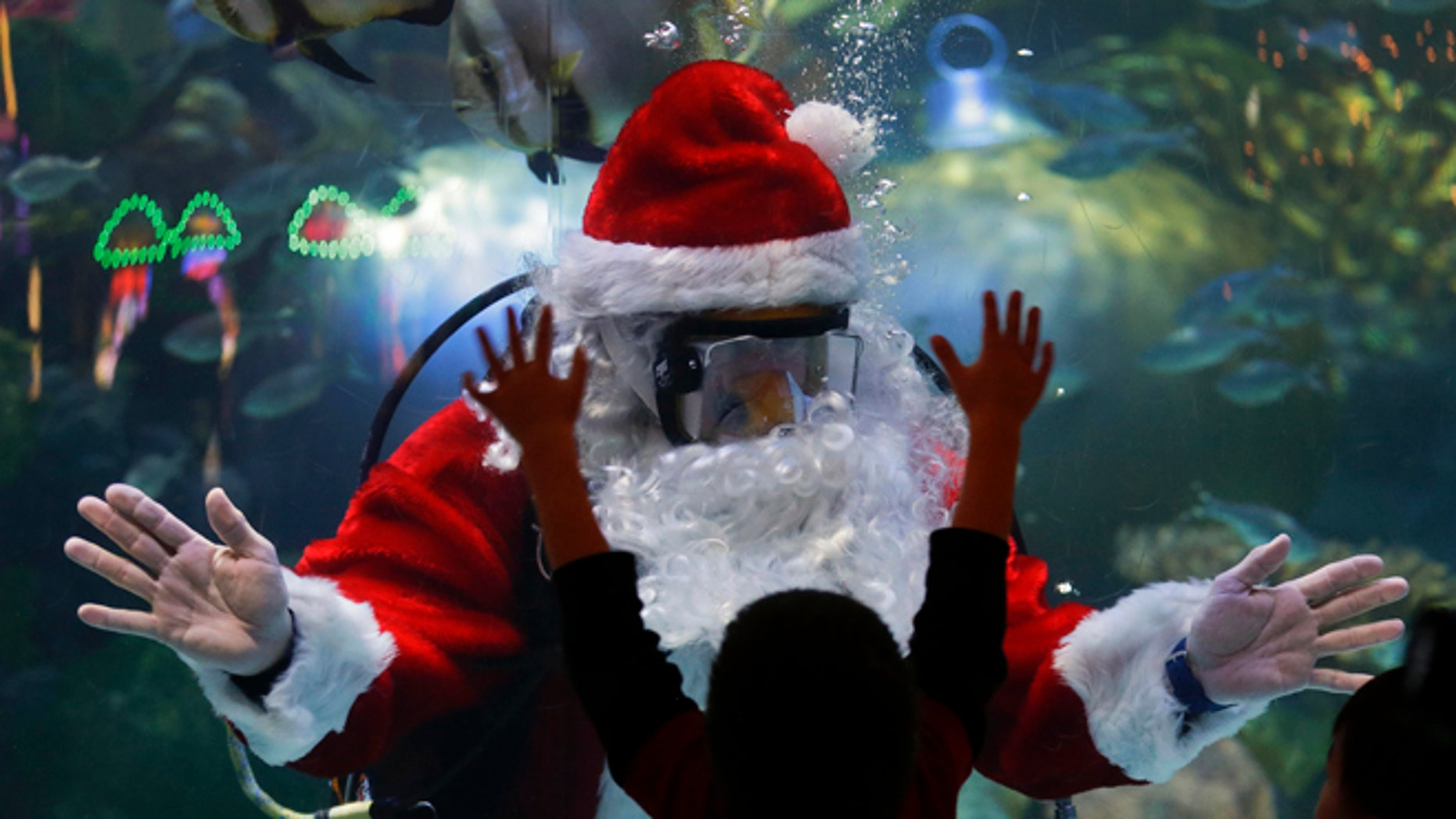 Jerry Cowley, aquatic safety manager at the Silverton Hotel-Casino interacts with children as an underwater Santa Claus, at the casino's aquarium in Las Vegas.