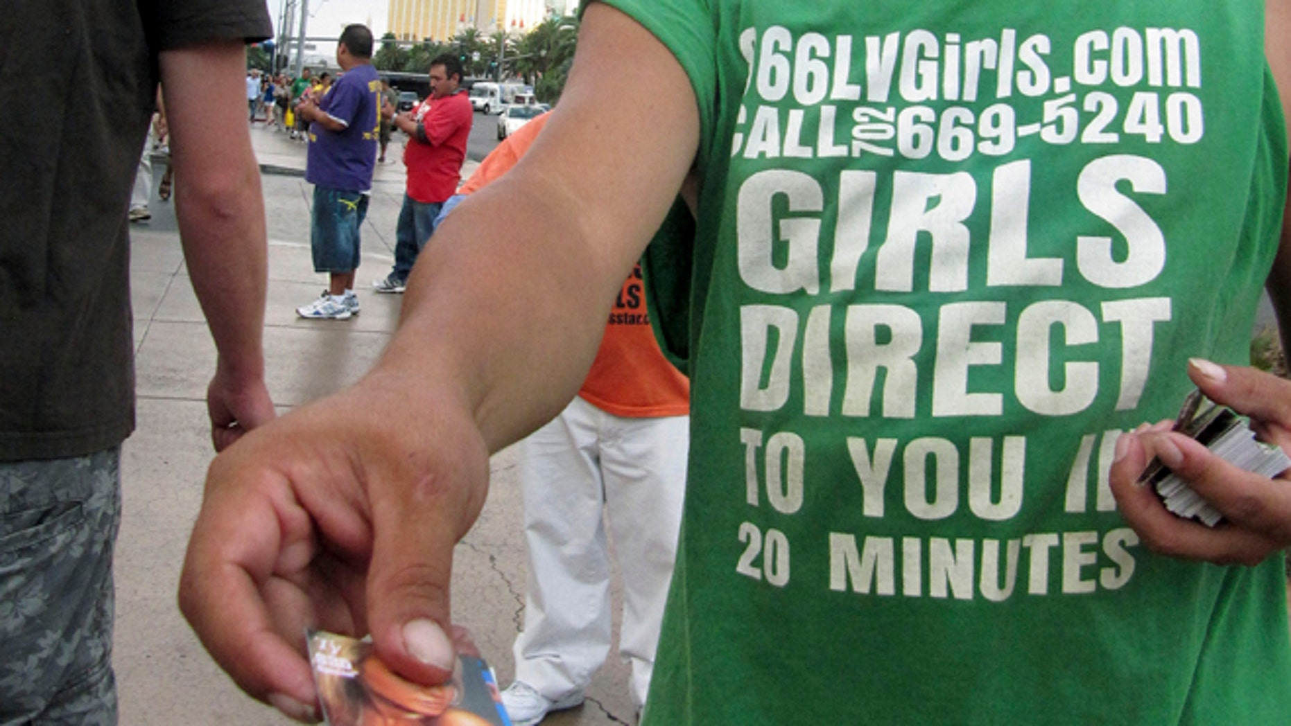 Aug. 29, 2012: An unidentified man on a Las Vegas Strip sidewalk hands out cards advertising exotic dancers.