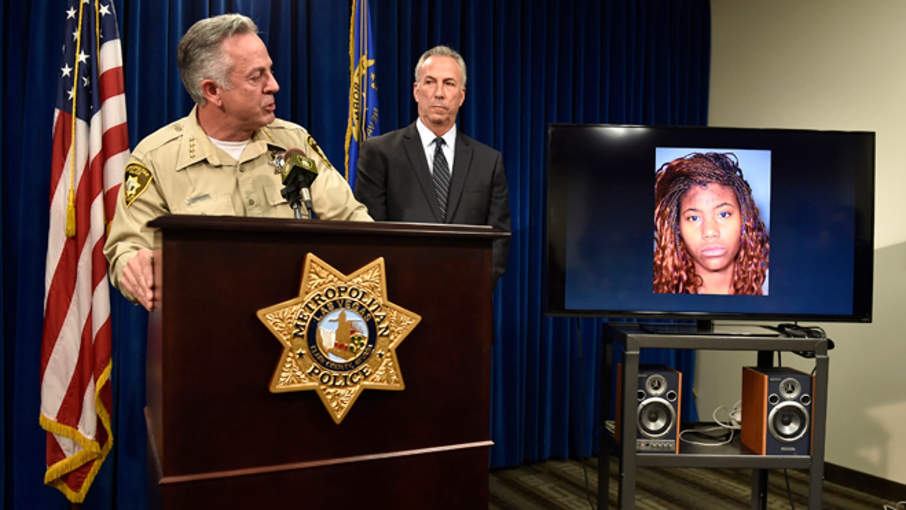 Clark County Sheriff Joe Lombardo, left, and Clark County District Attorney Steve Wolfson attend at a news conference, Monday, Dec. 21, 2015, in Las Vegas. The two officials spoke about the car driven by suspect Lakeisha N. Holloway, pictured on monitor, of Oregon, who police said smashed into crowds of pedestrians on the Las Vegas Strip on Sunday night, killing one person and injuring dozens. (AP Photo/David Becker)