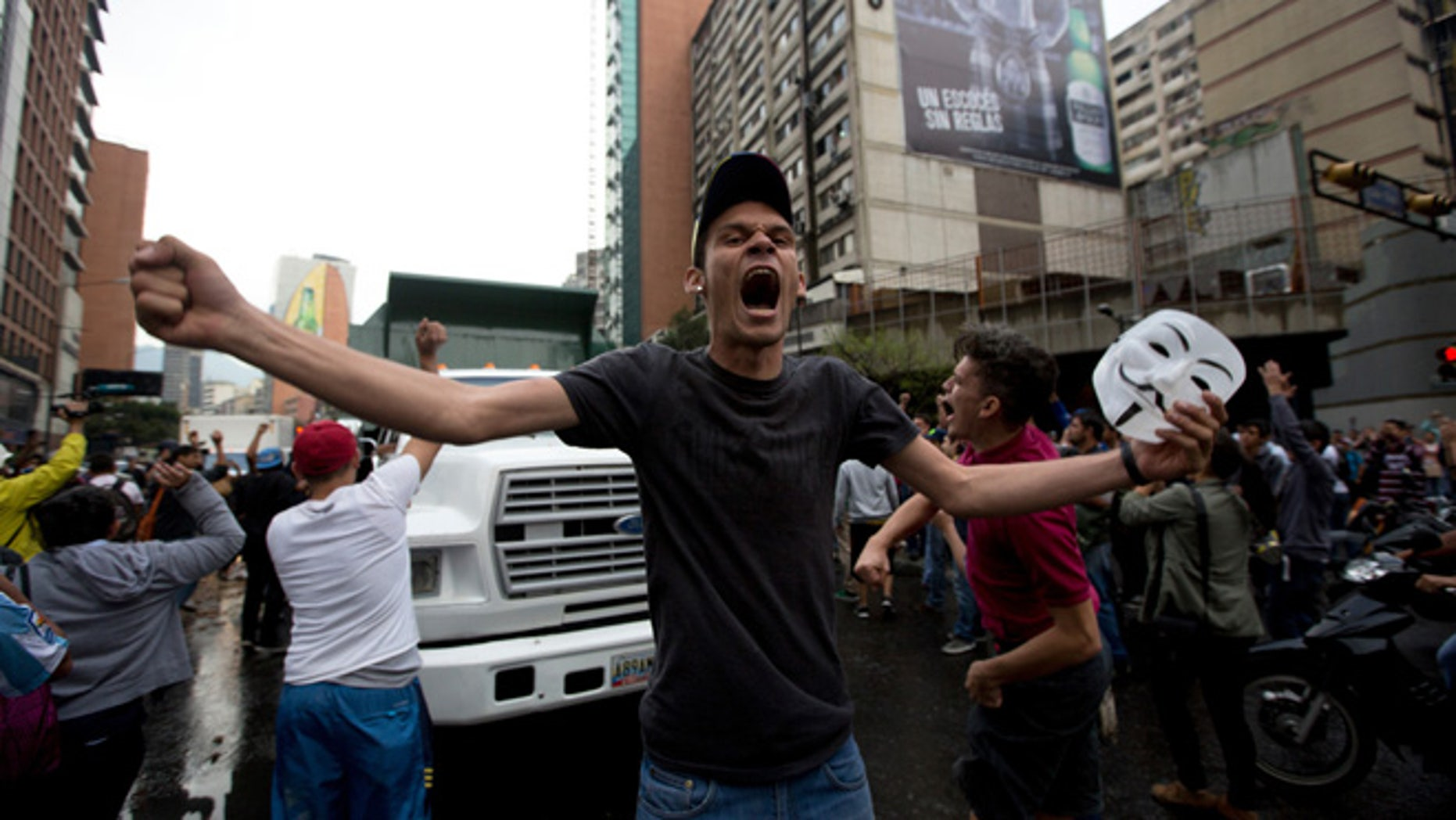 A demonstrator shouts slogans against Venezuela's President Nicolas Maduro as protesters block a road in Caracas, Venezuela, Thursday, Feb. 12, 2015. Venezuelans staged dueling marches to mark the anniversary of last year's bloody protest movement that resulted in more than 40 people being killed, including both government supporters and opponents. Dozens of protesters remain jailed, while the social issues they railed against last year- a faltering economy, widespread shortages and pervasive violent crime - have only gotten worse. (AP Photo/Fernando Llano)