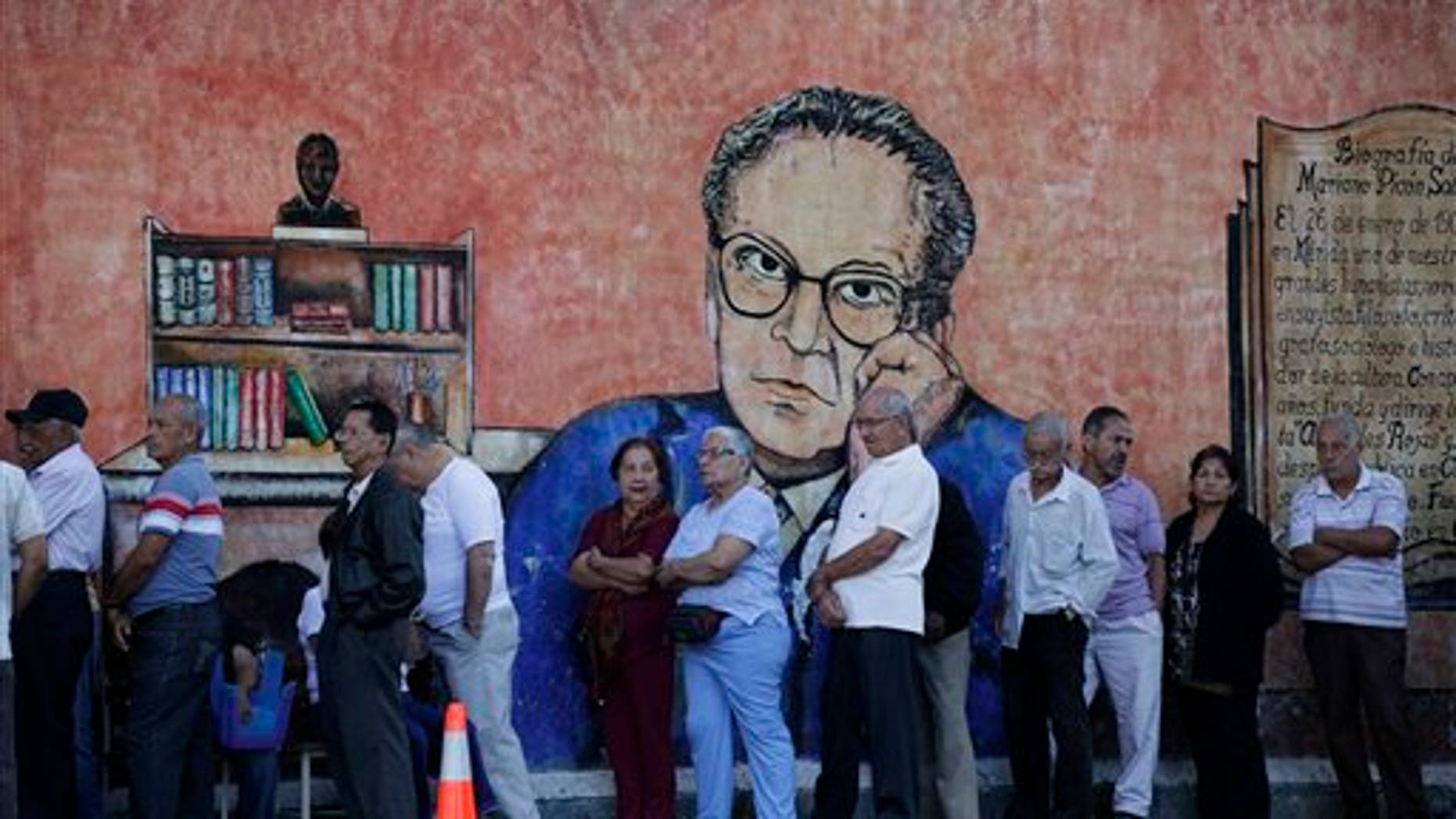 Residents in front of a wall with a painting depicting Venezuelan writer and diplomat Mariano Picon as they wait in line to enter a polling station to vote during municipal elections in Caracas, Venezuela, Sunday, Dec. 8, 2013. Venezuelans head to the polls to elect mayors and city councilors at a moment when the country's economic troubles have deepened, with inflation touching a two-decade high of 54 percent, and shortages of everything from toilet paper to milk spreading while the black market value of the currency plunges.  (AP Photo/Ariana Cubillos)