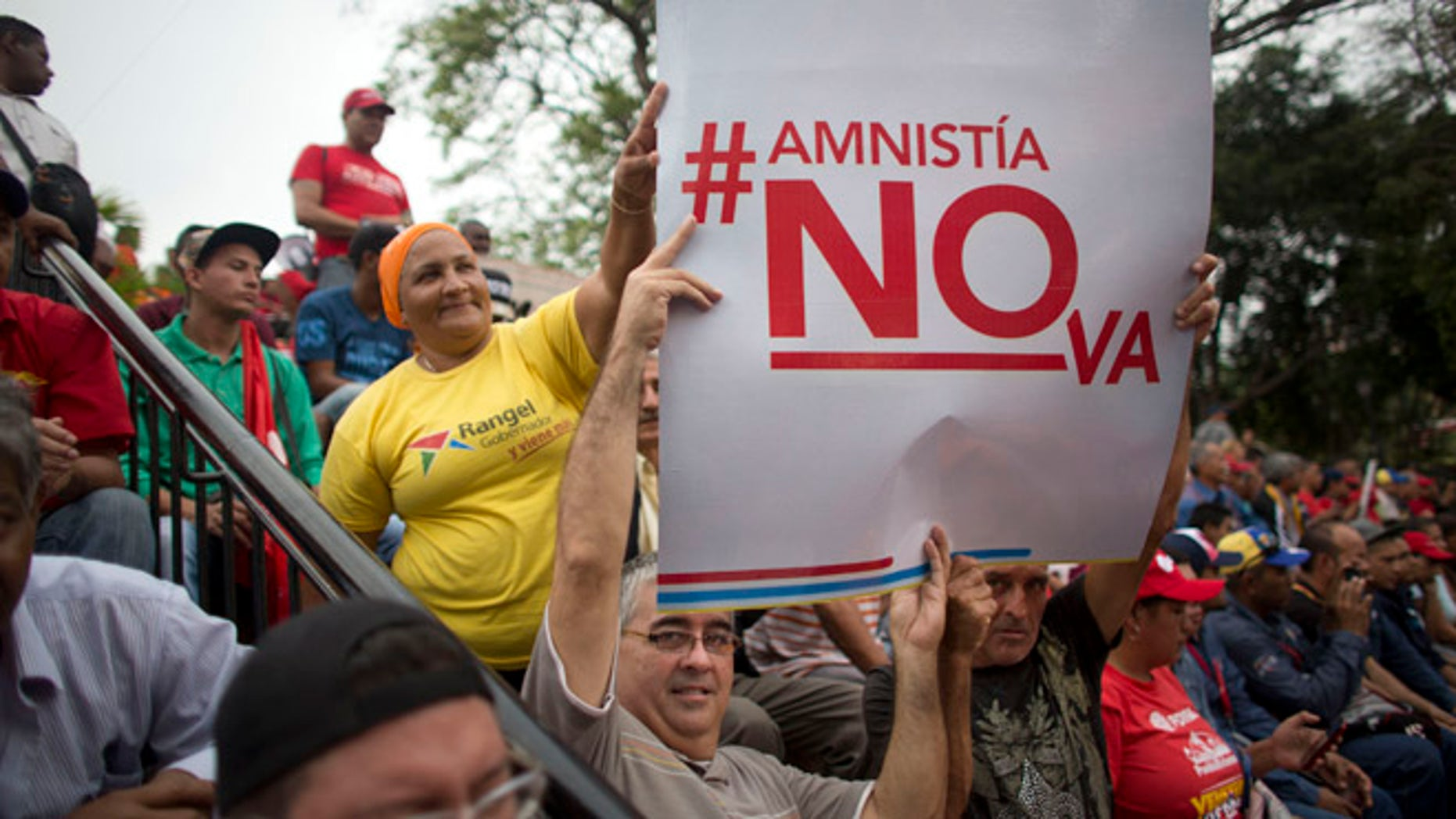 """Supporters of President Nicolas Maduro hold a sign that reads in Spanish """"Amnesty will not go"""" during a march, at Miraflores Presidential Palace in Caracas, Venezuela, Thursday, April 7, 2016. Groups allied to Venezuela's socialist administration marched to protest an amnesty law passed by the opposition controlled congress calling for release of those it deems to be political detainees. (AP Photo/Ariana Cubillos)"""