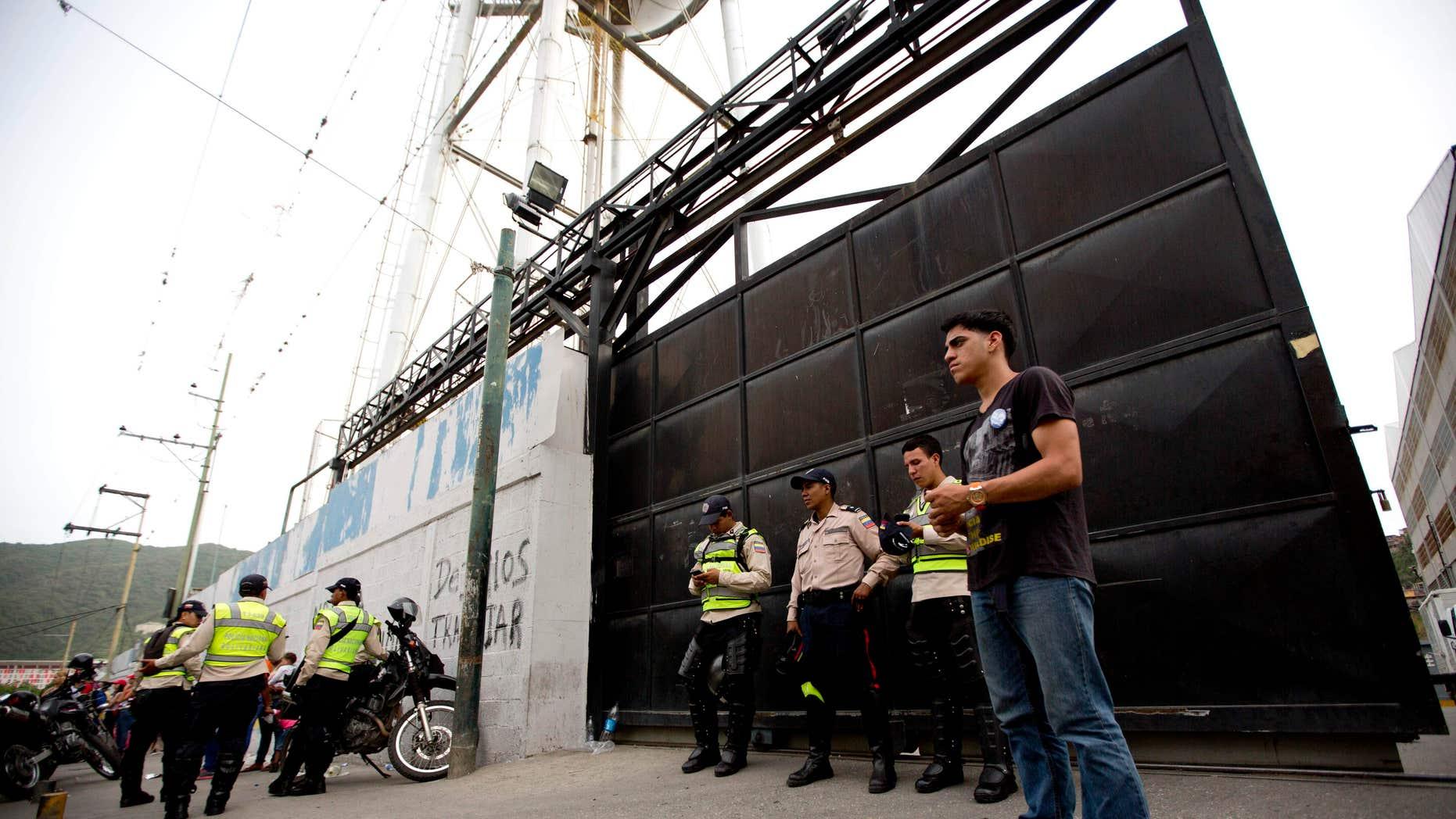 Bolivarian Police officers at the gate of distribution center  of Empresas Polar, in Caracas, Venezuela, Thursday, July 30, 2015.