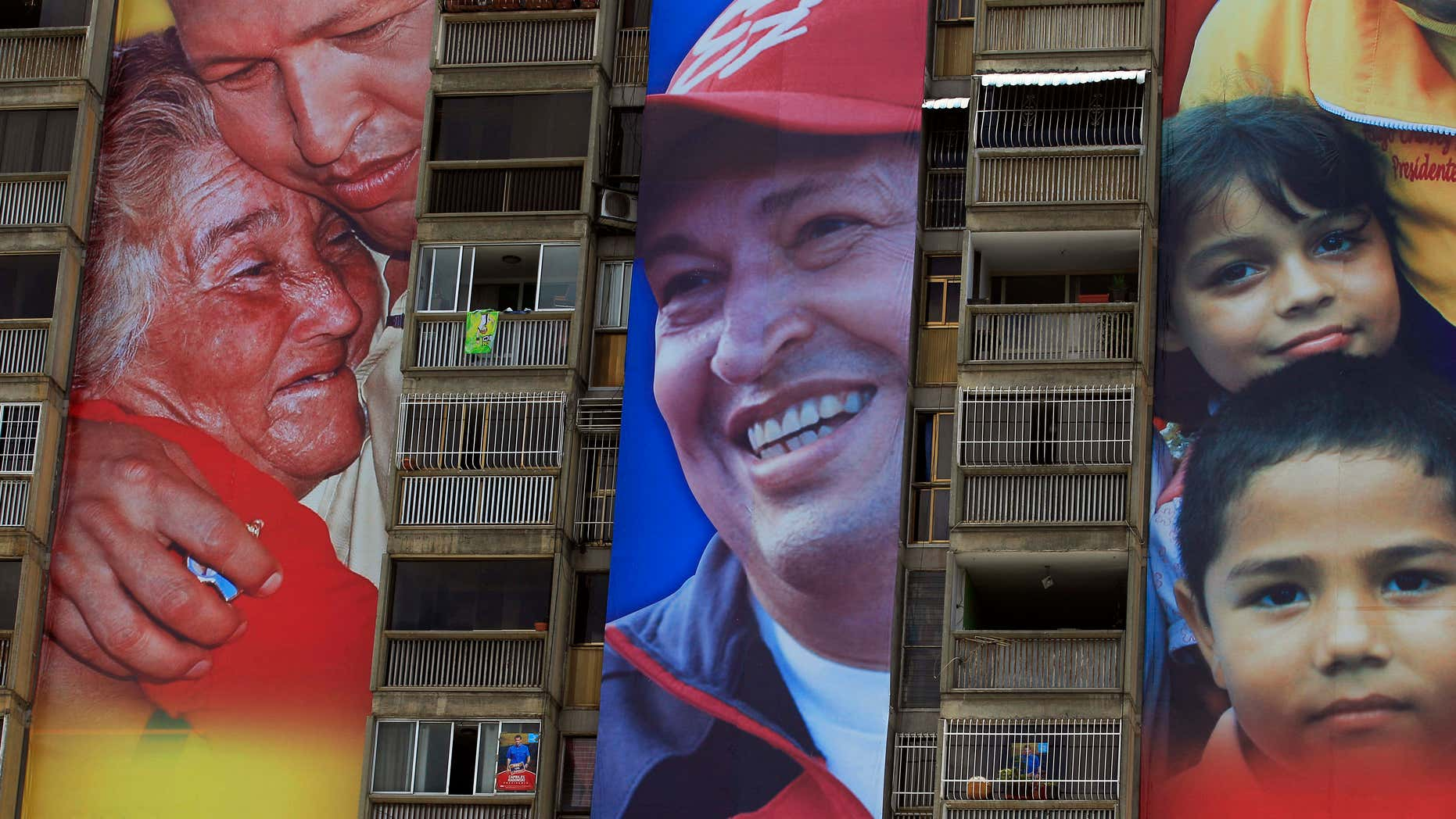 Campaign re-election posters of Venezuela's President Hugo Chavez tower over the posters of opposition presidential candidate Henrique Capriles, on an apartment building in Caracas, Venezuela, Tuesday, Aug. 21, 2012.  A little more than a month ahead of Venezuela's Oct. 7, election, Chavez enjoys clear advantages over his challenger in campaign funding and media access. While neither campaign has revealed how much it's spending, Capriles says he is in a David versus Goliath contest, facing a well-financed incumbent backed by an even richer government. (AP Photo/Fernando Llano)