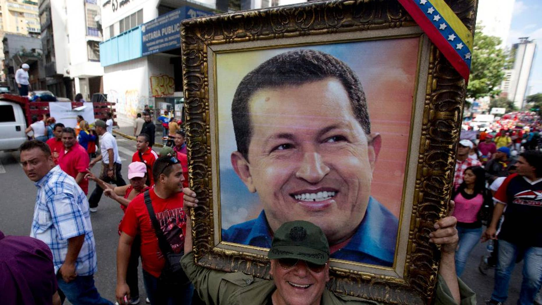 In this Feb. 28, 2015 photo, a man holds a framed image of the late President Hugo Chavez during a pro-government rally outside of the Miraflores presidential palace in Caracas, Venezuela. Venezuelans are commemorating Hugo Chavez on the second anniversary of his death, Thursday, March 5, 2015, even as an economic crisis threatens to undo the former president's legacy of lifting thousands out of poverty. (AP Photo/Fernando Llano)