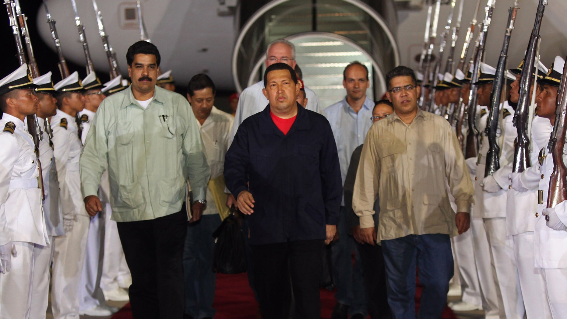 July 23, 2011:  In this file photo, released by Miraflores Presidential Press Office, Venezuela's President Hugo Chavez, center, accompanied by Foreign Minister Nicolas Maduro, front left, and Vice President Elias Jaua, front right, arrive to the airport in Maiquetia, Venezuela.