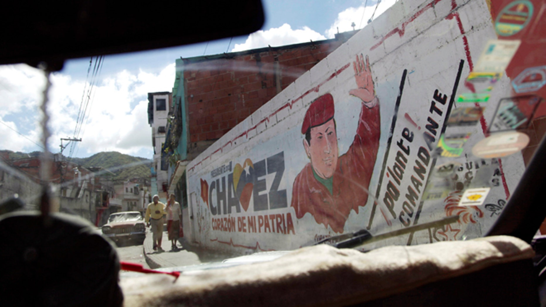 """The windshield of a car frames a mural of Venezuela's President Hugo Chavez in Caracas, Venezuela, Wednesday, Jan. 2, 2013.  Venezuela's vice president is returning home Wednesday from a visit with Chavez in Cuba and says the ailing president's condition remains """"delicate"""" three weeks after his cancer surgery. (AP Photo/Ariana Cubillos)"""