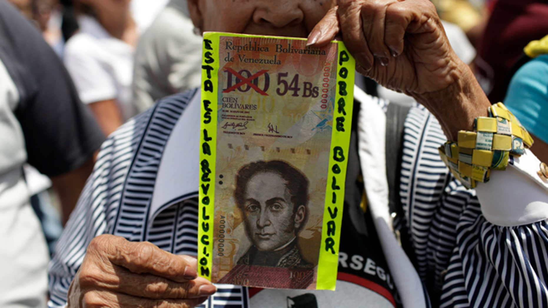 """An anti-government protester holds up a fake Venezuelan banknote that reads in Spanish, """"This is the revolution. Poor Bolivar."""""""